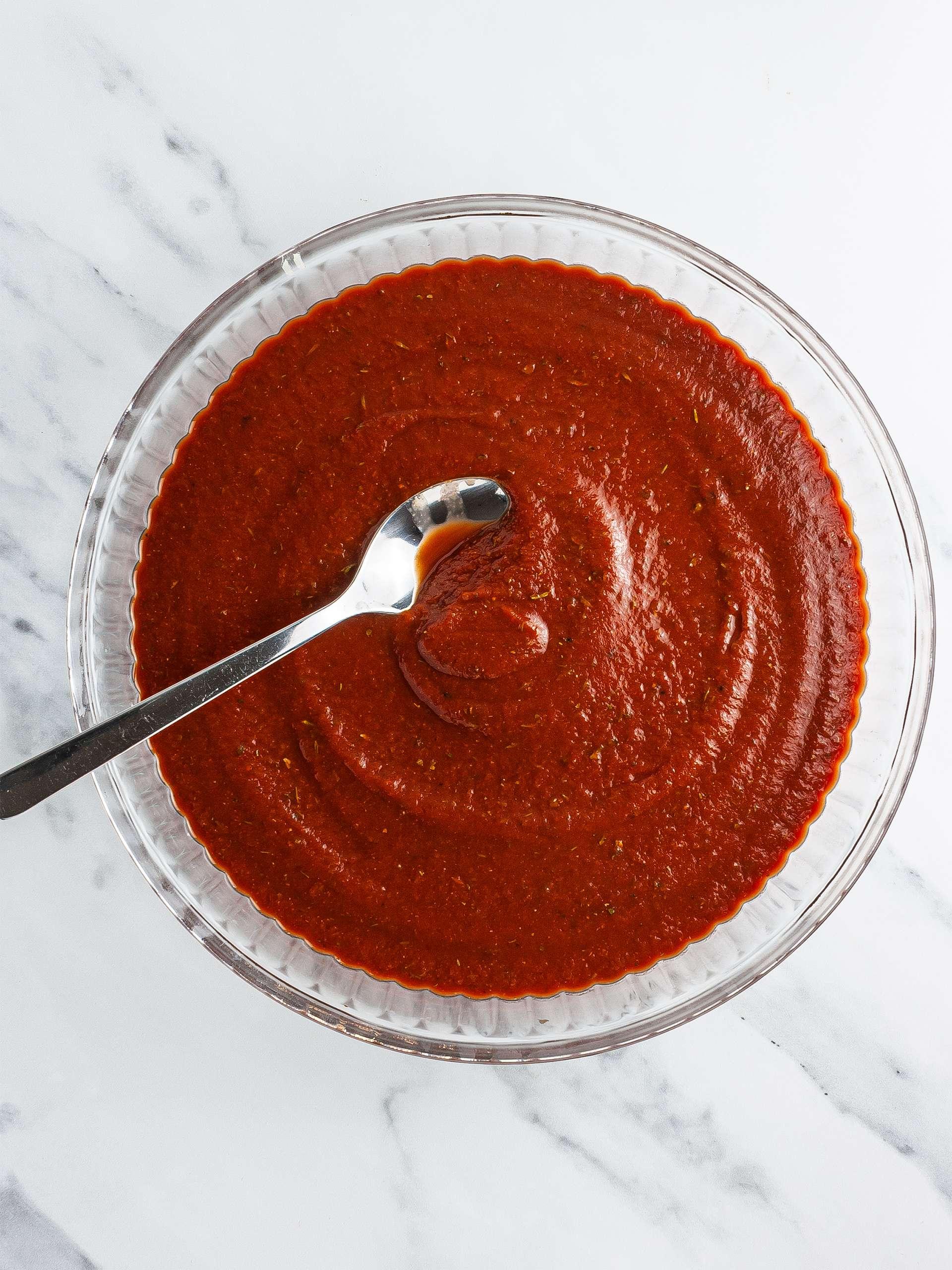 Tomato sauce spread over a baking dish