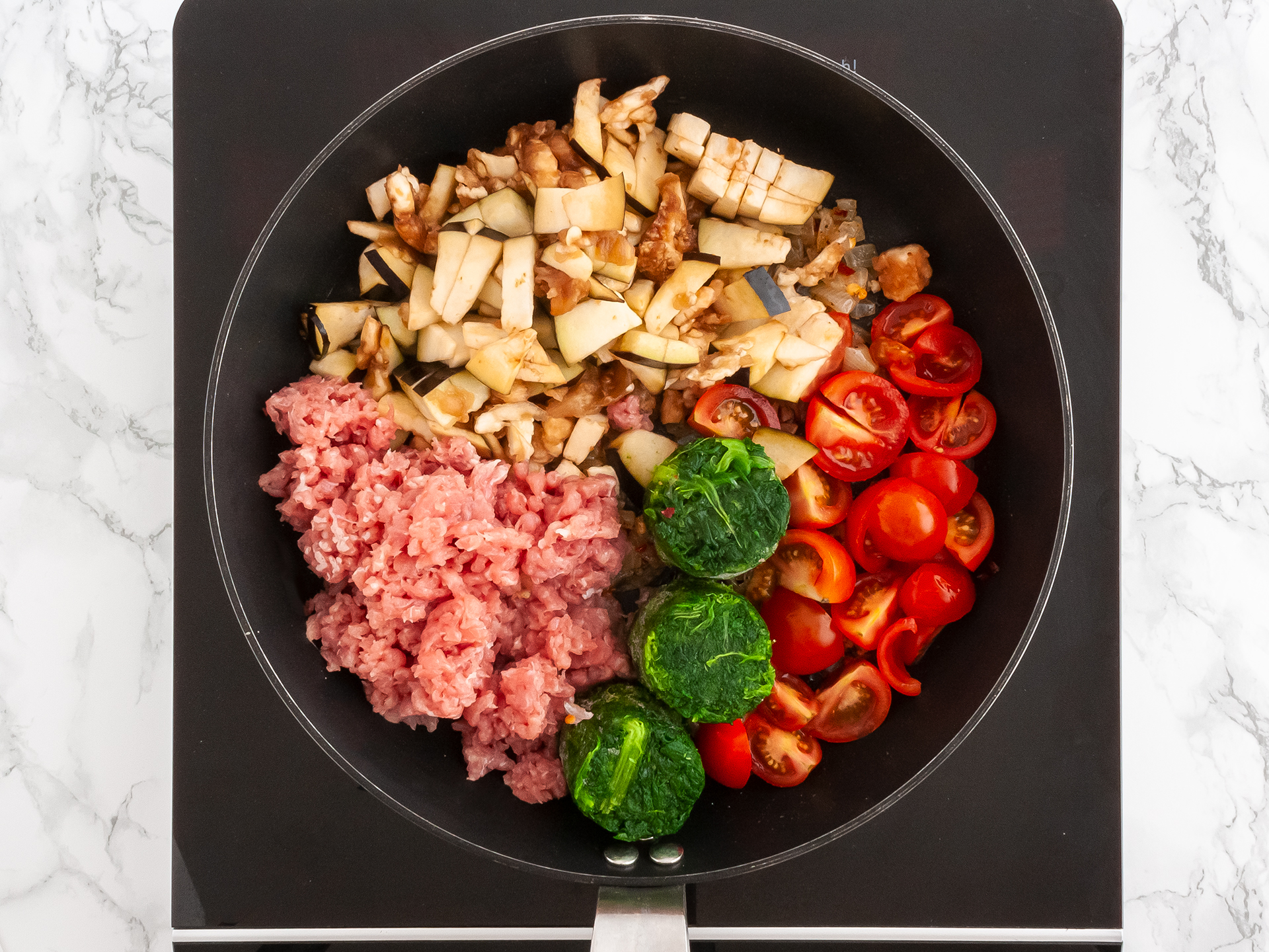 Mince, spinach, tomatoes and aubergines and other keto aubergine ingredients inside a pan