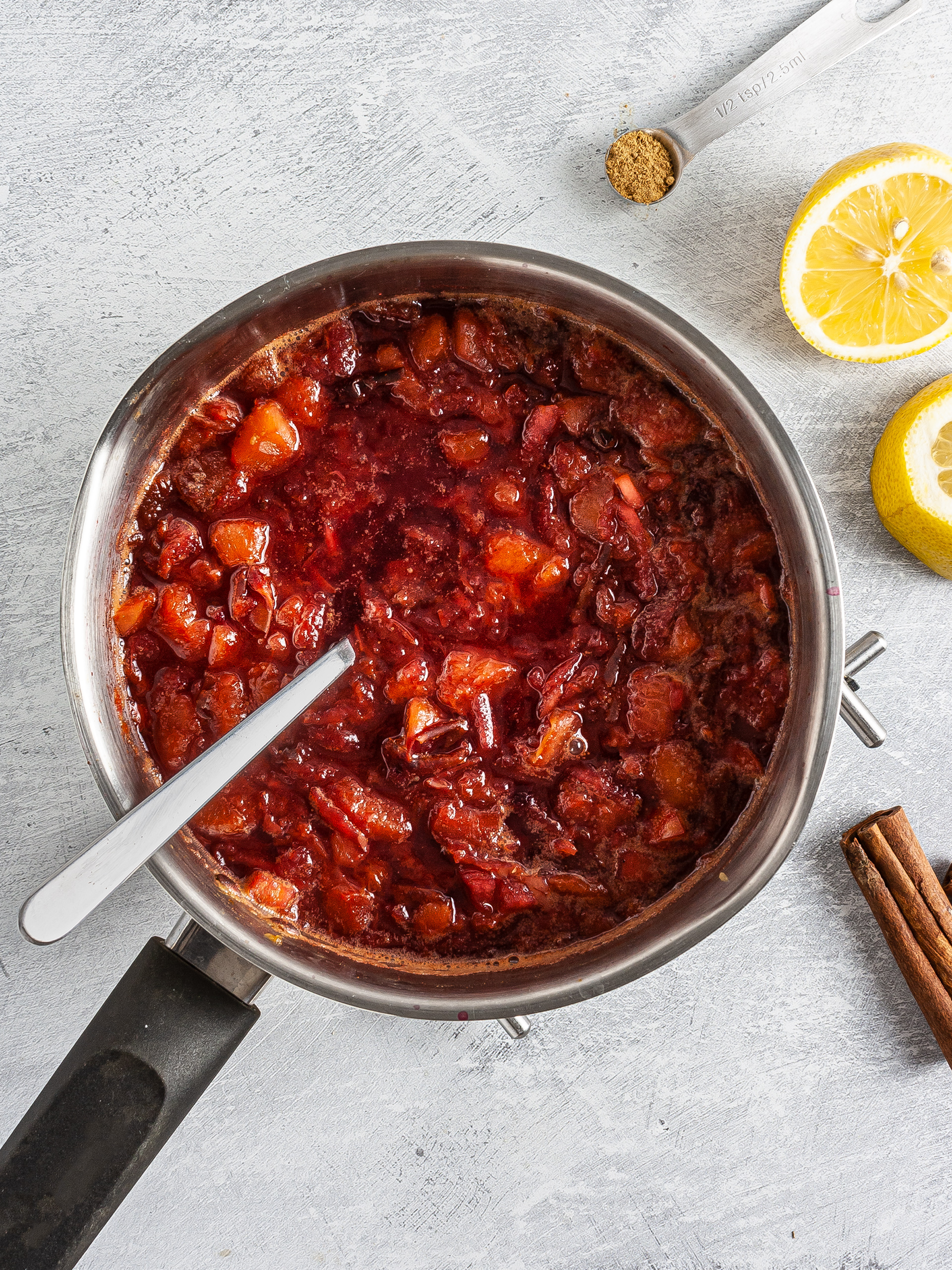 Plums, apple, cinnamon, and lemon cooking in a pan.