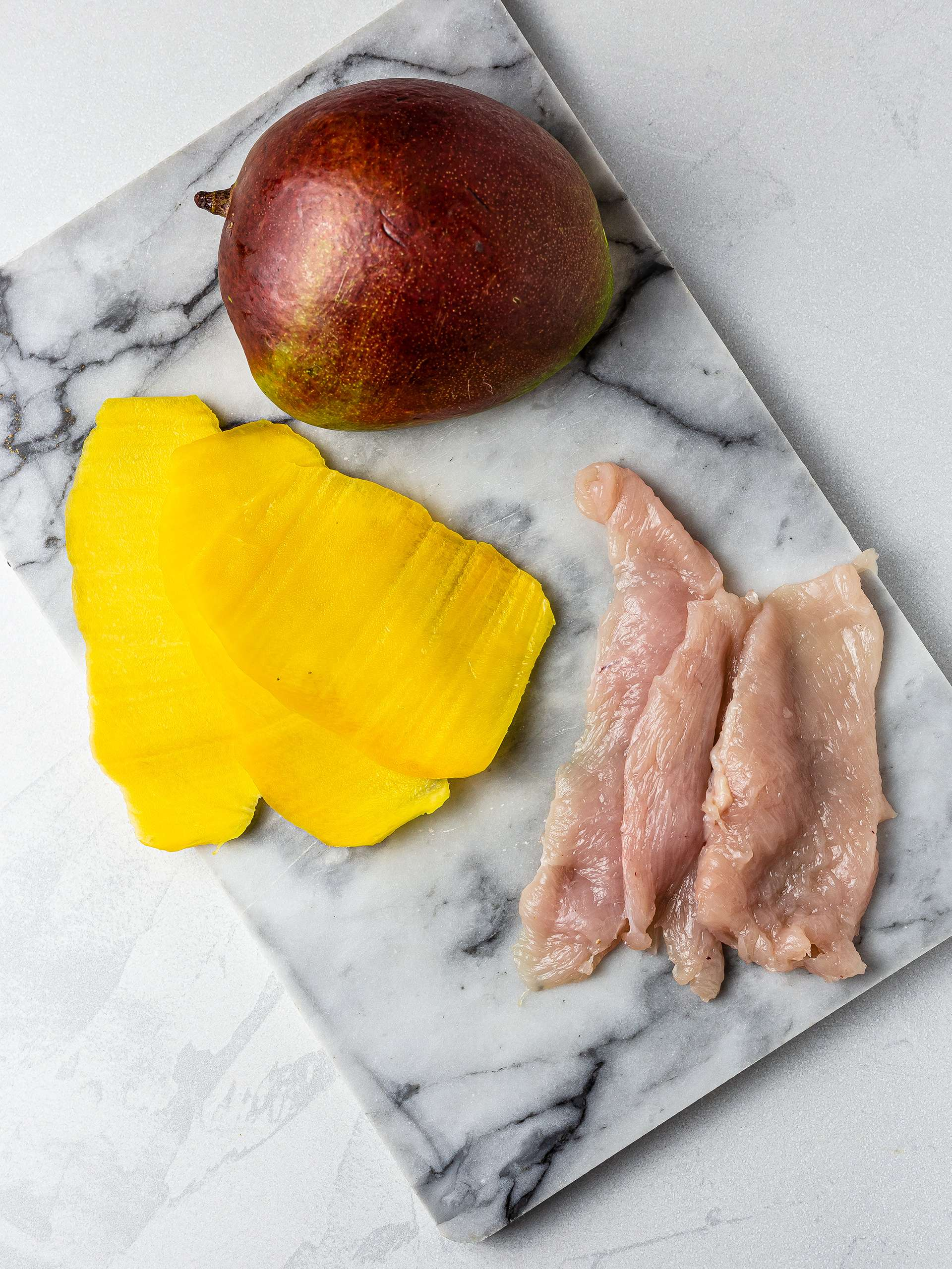 Sliced mango and chicken breast