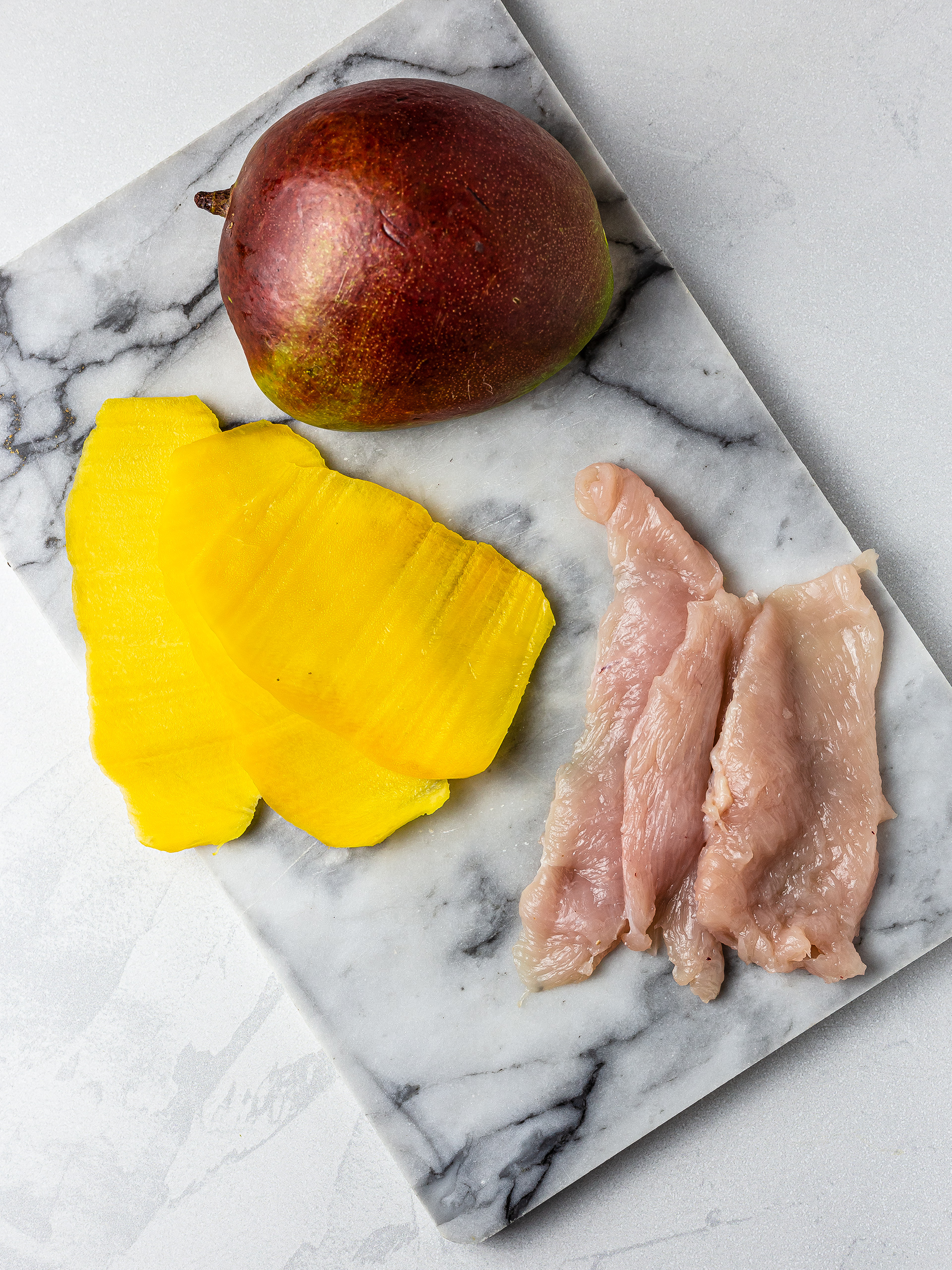 Sliced mango and chicken breast