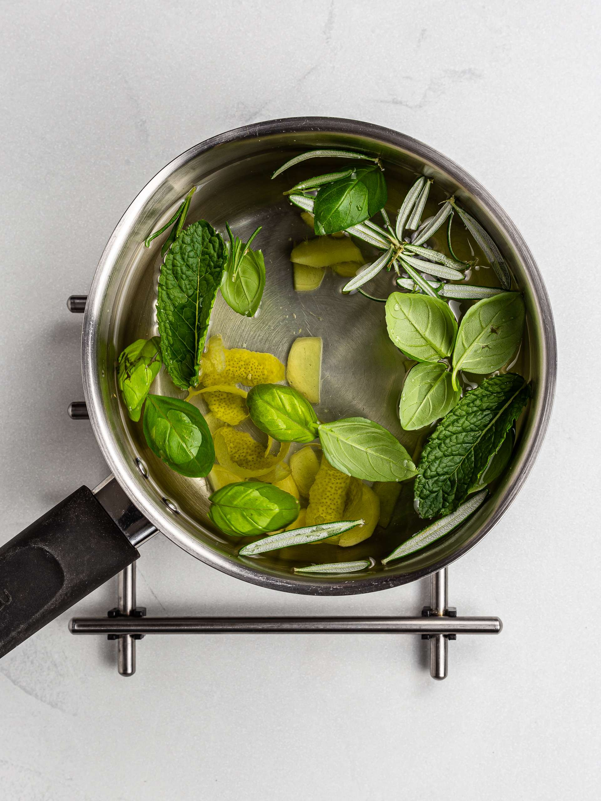 fresh herbs in a pot of water with ginger and lemon peel