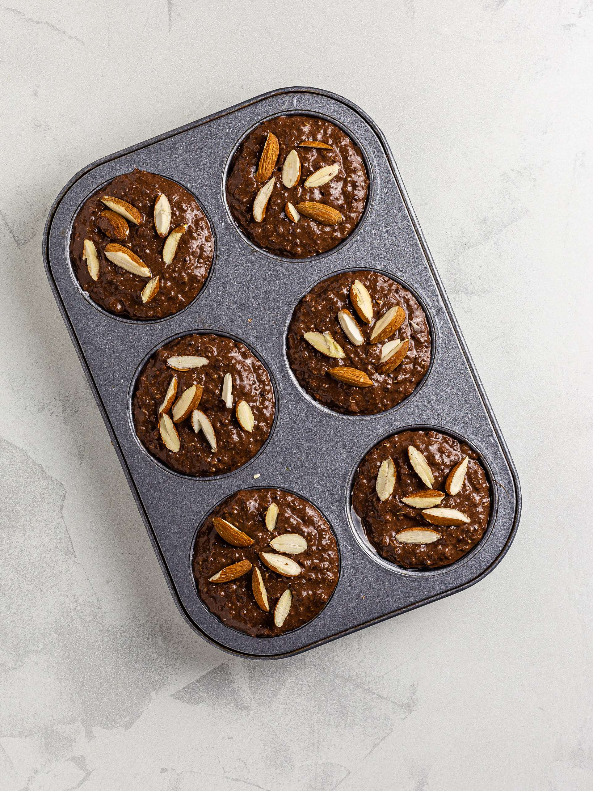 chocolate muffins in a muffin tin with almonds
