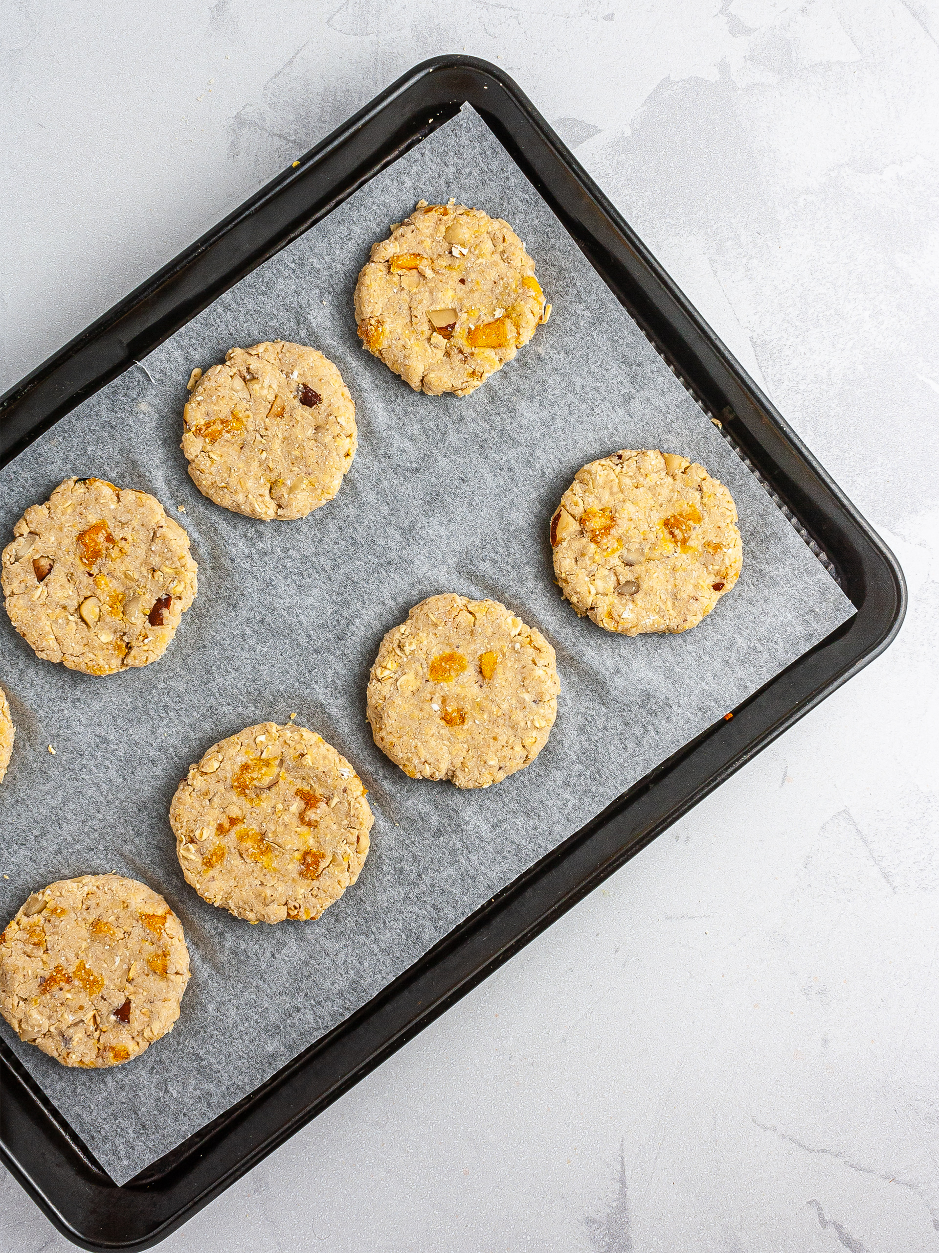 Dough shaped into cookies over a baking tray.