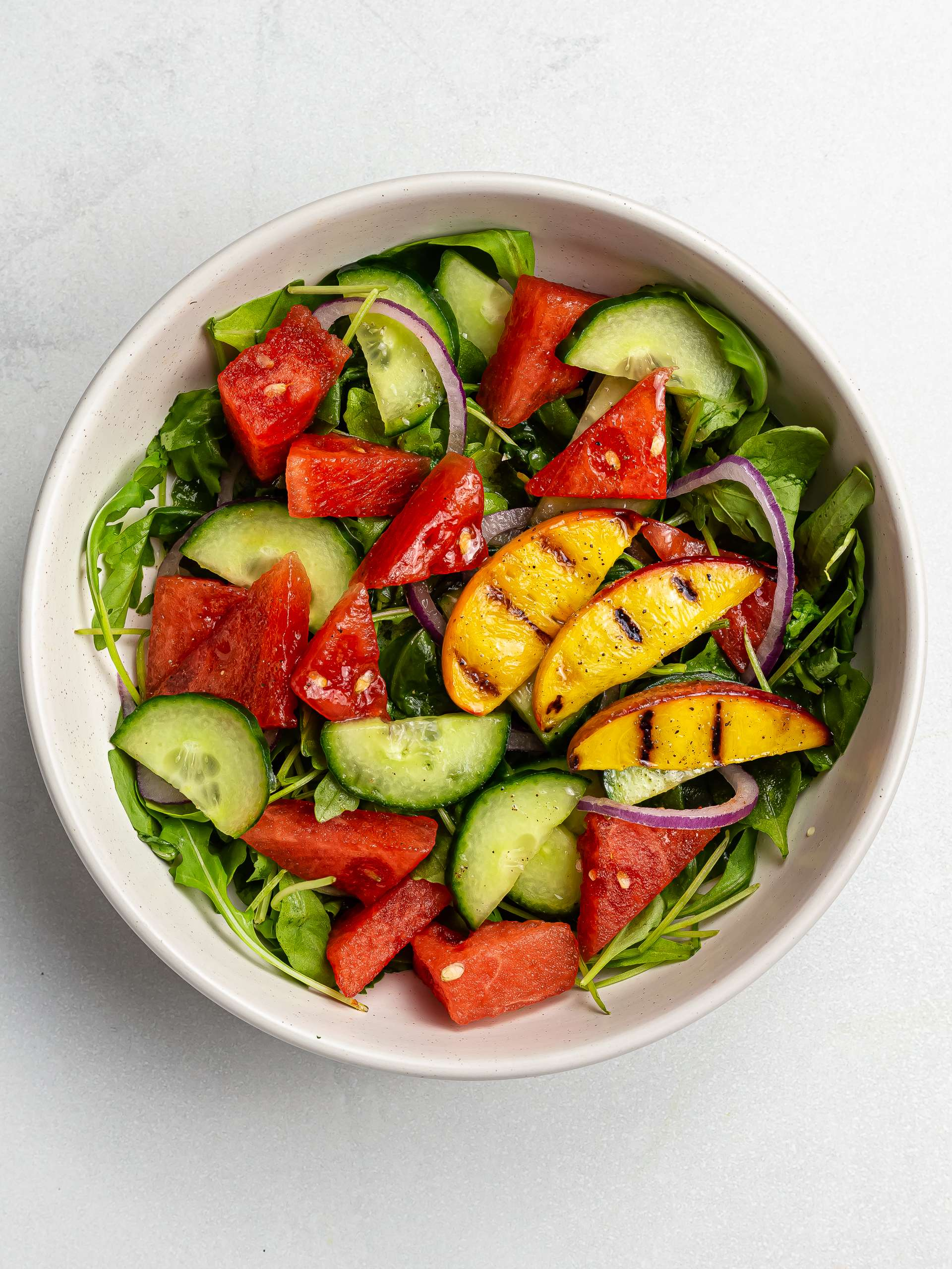 watermelon arugula salad with grilled peaches in a bowl