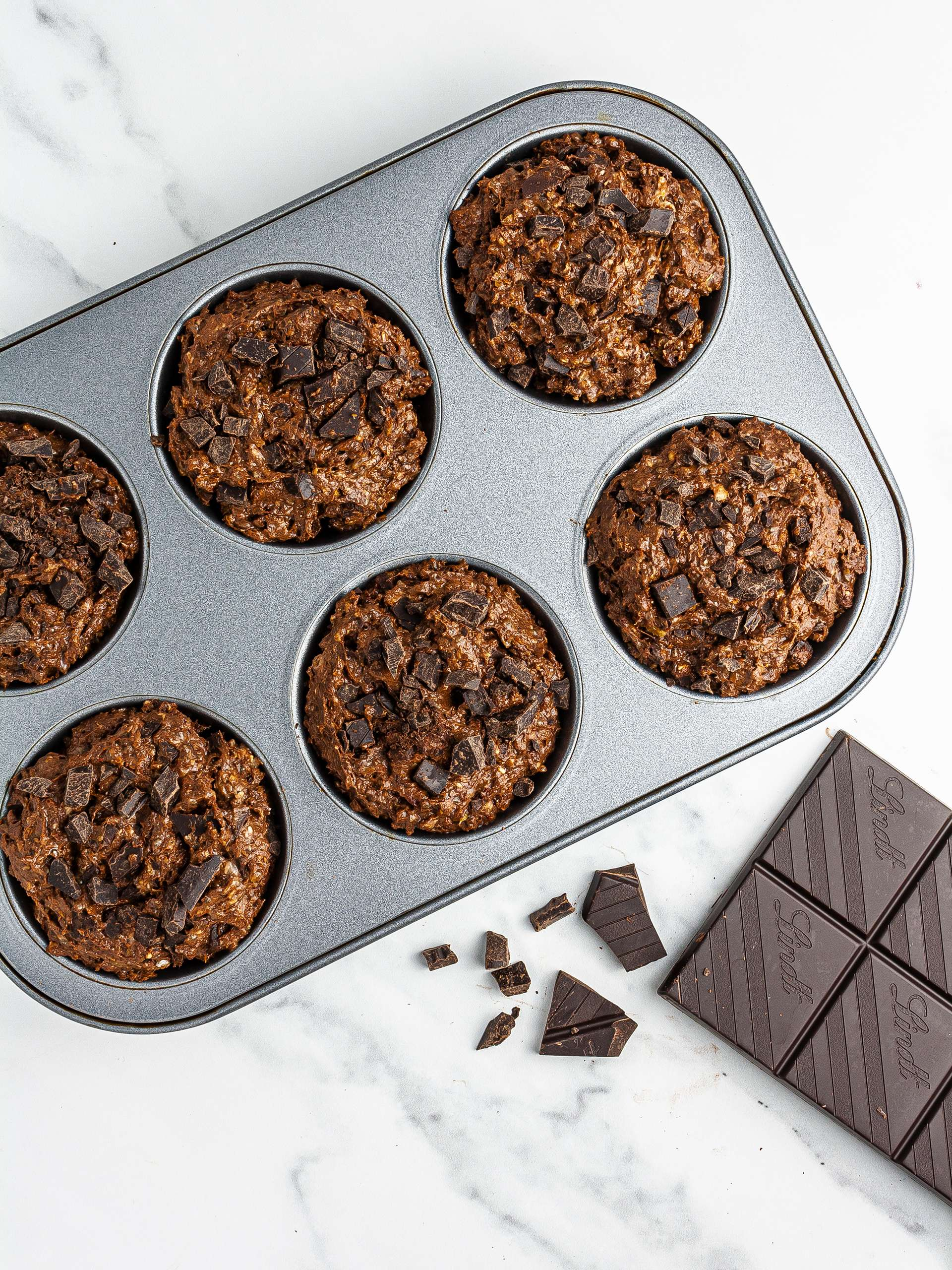 Muffin dough in baking tray with chocolate chips