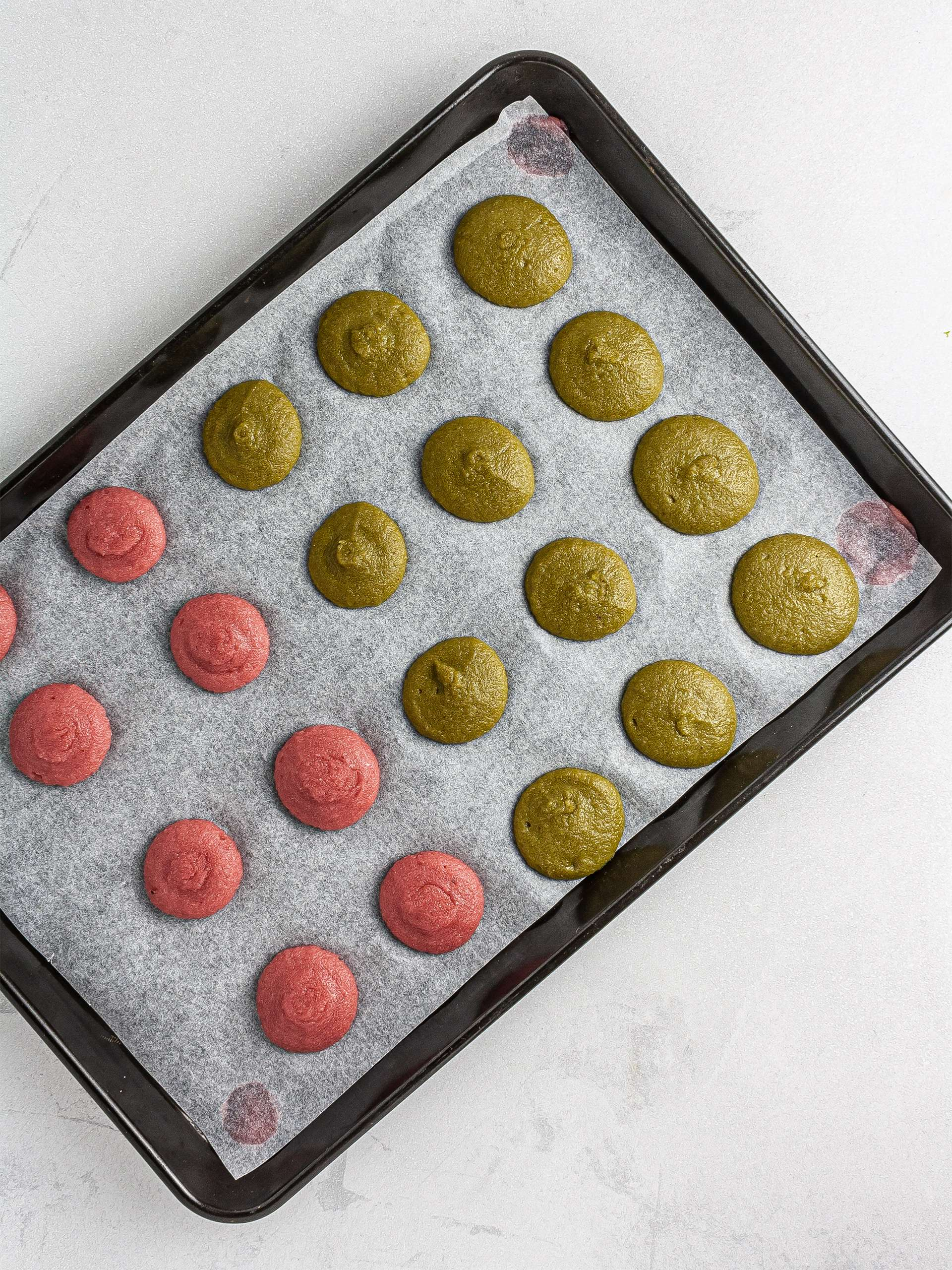Macaron batter piped over baking tray