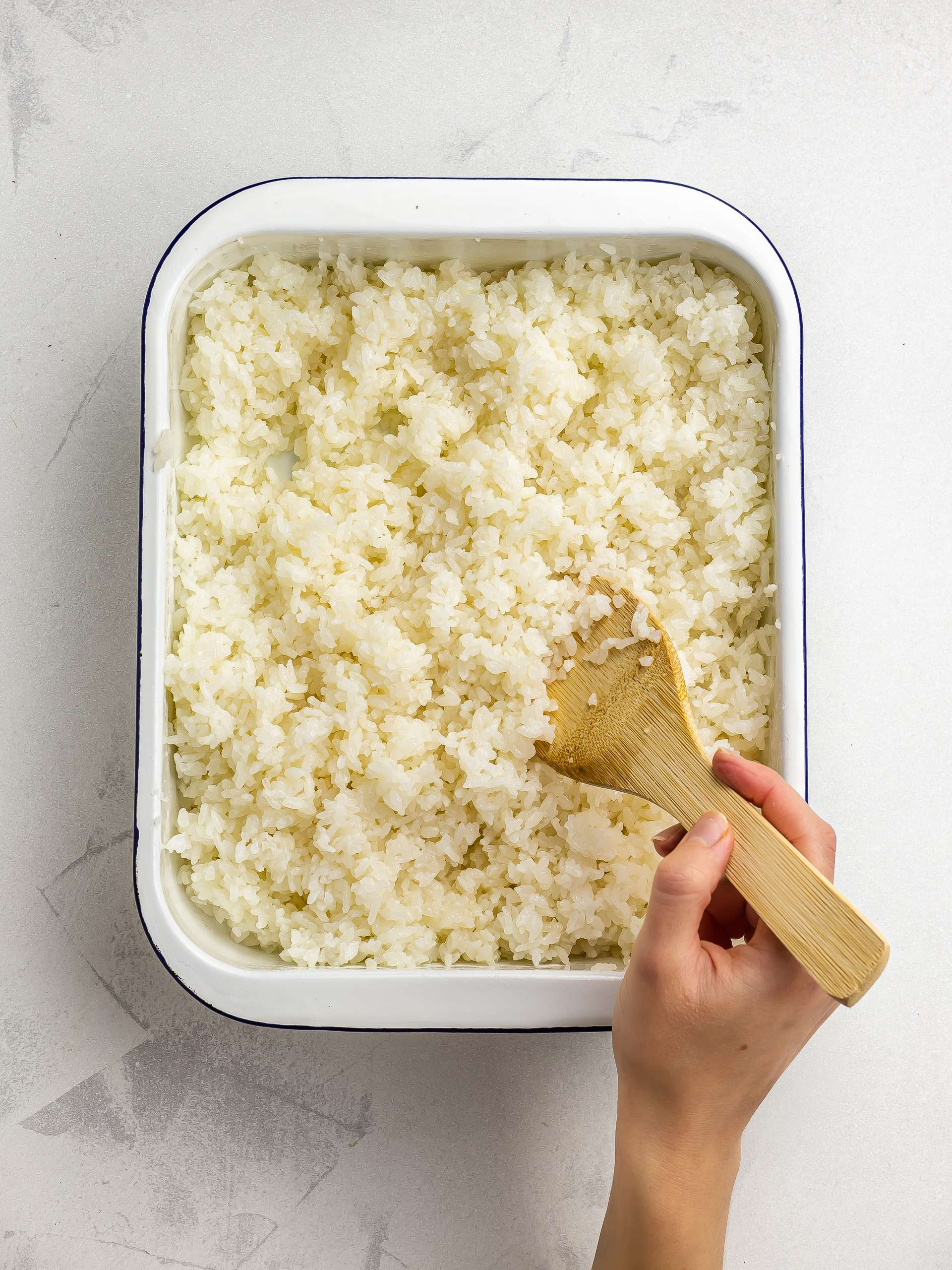 cooling down and mixing sushi rice with paddle