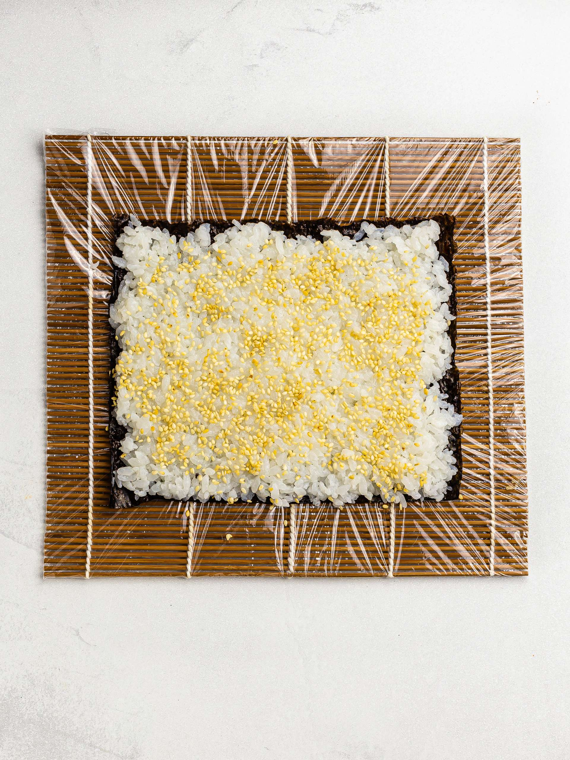 nori sheet with rice and sesame seeds