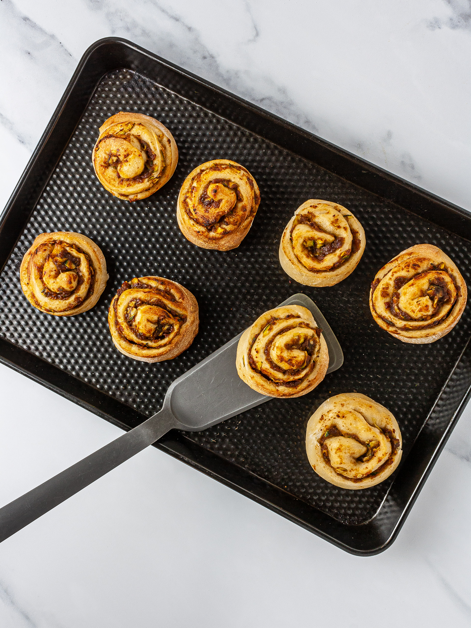 Baked zucchini cinnamon buns on tray.