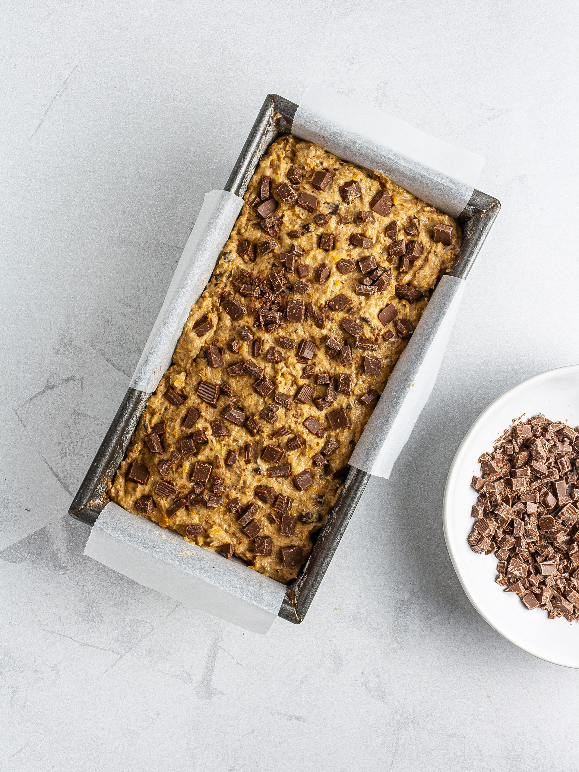 Pumpkin bread batter in loaf tin with chocolate chips