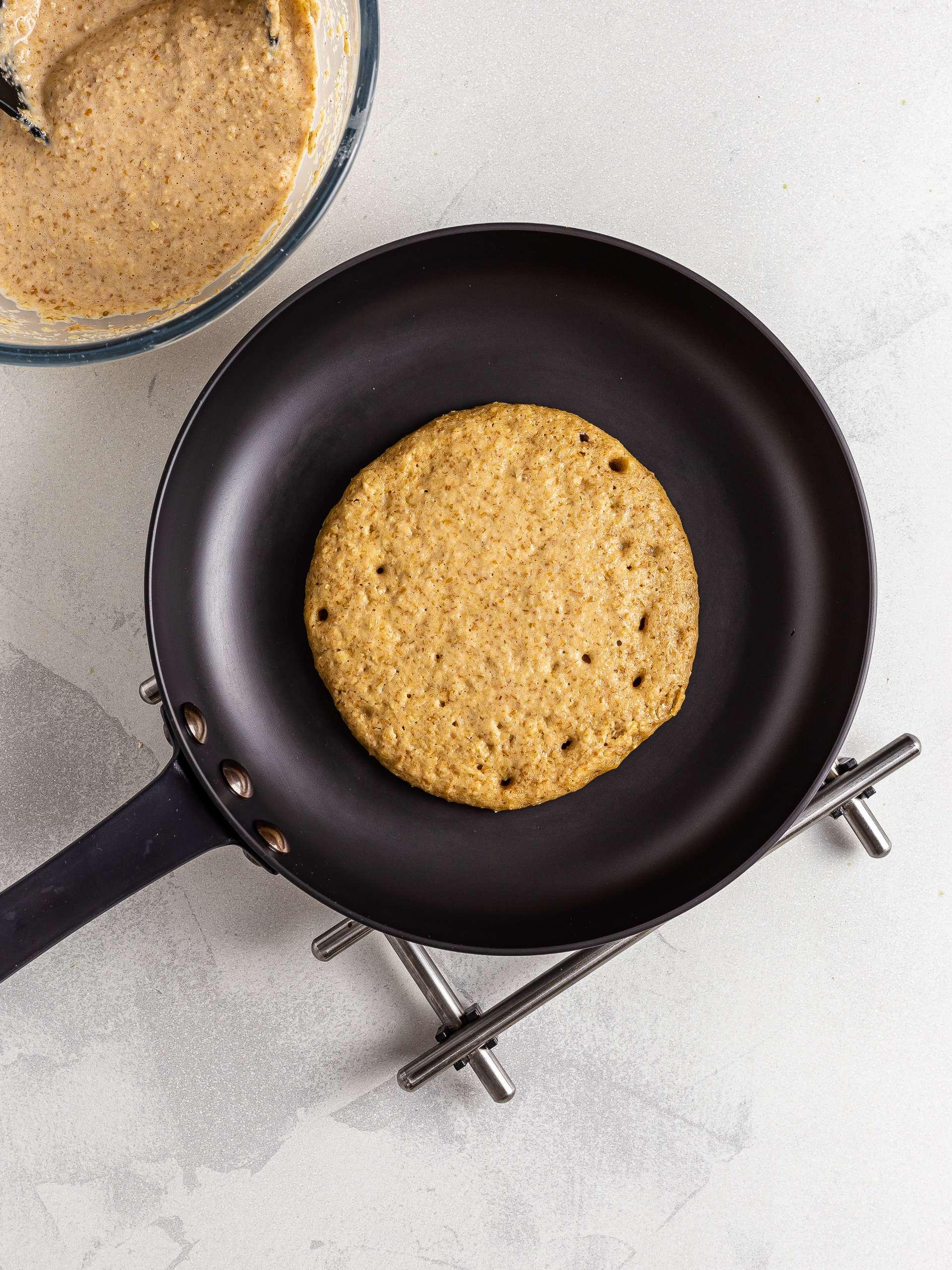 Lentil pancakes cooking in a skillet