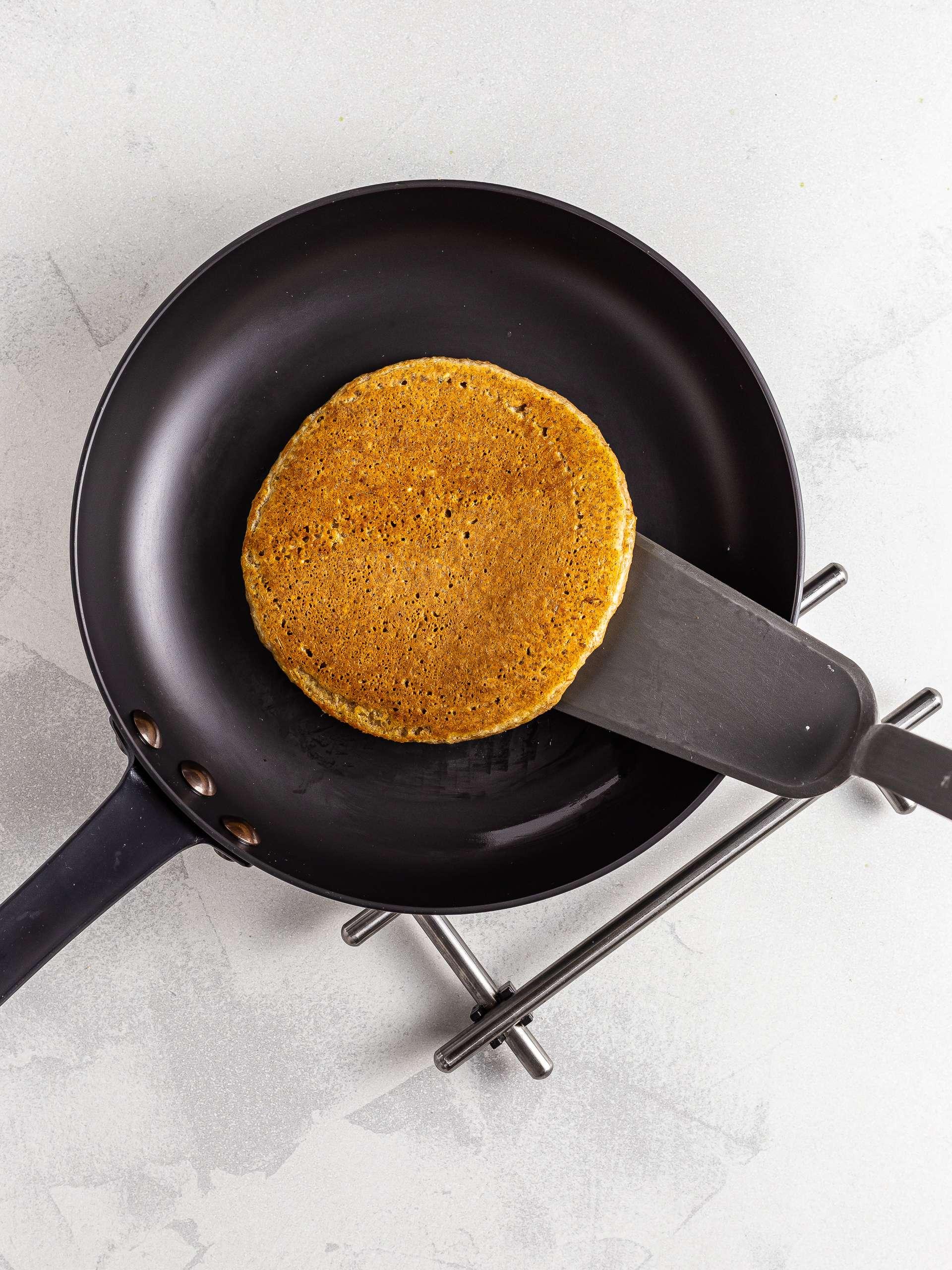 Flipped lentil pancakes in a skillet