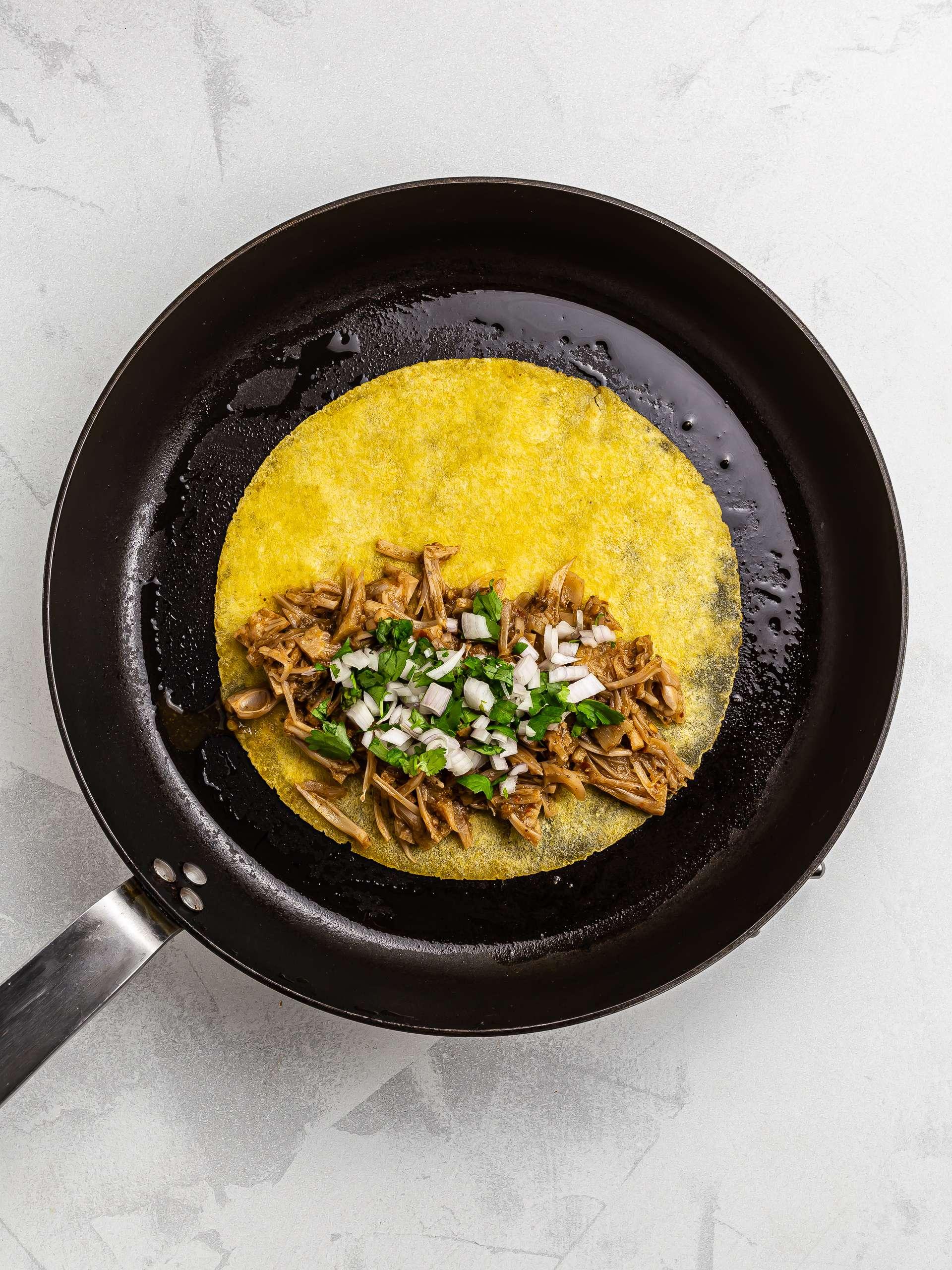 cooking jackfruit birria tacos in a skillet