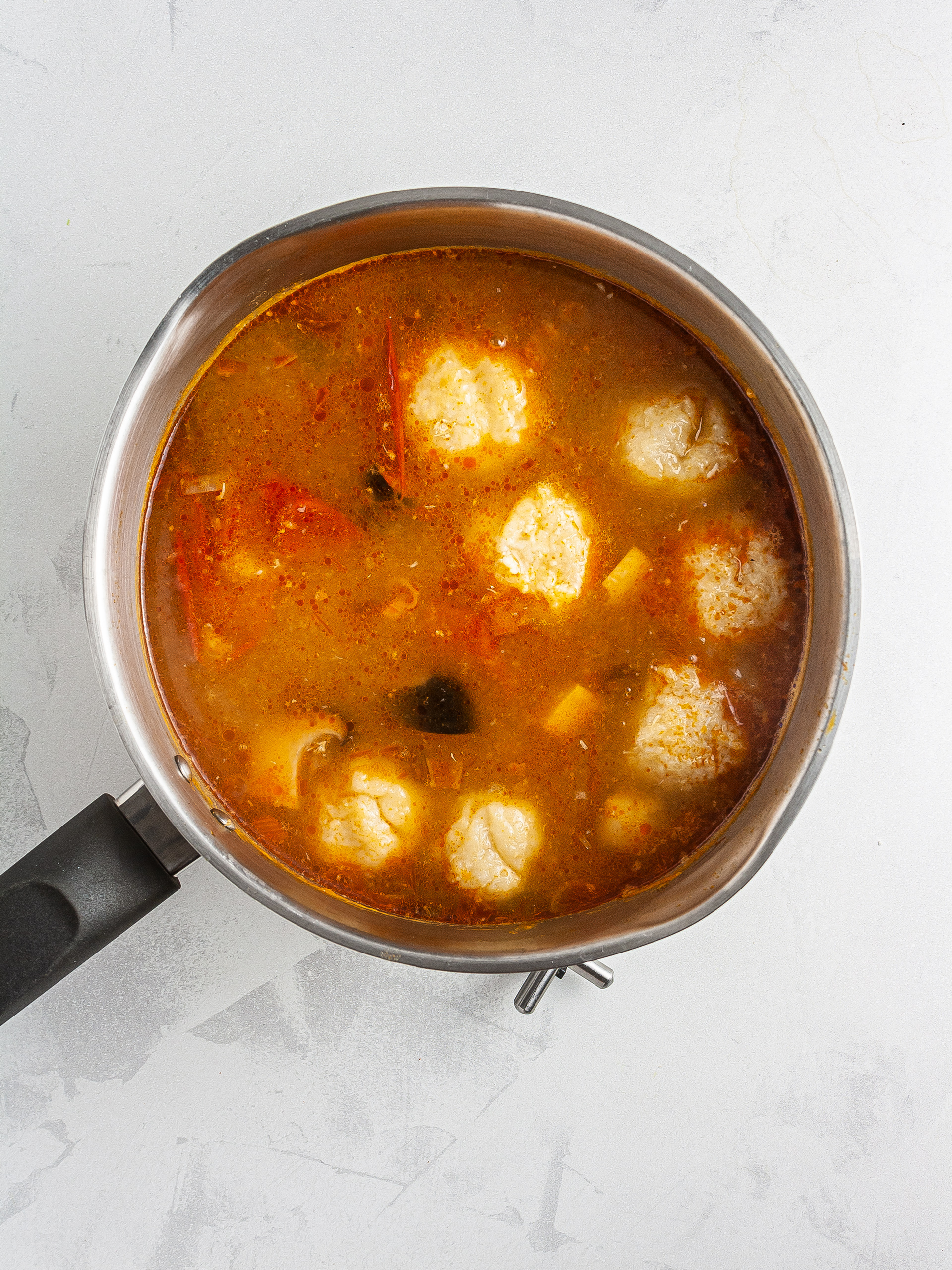 Crab balls in cooking in tomato stock