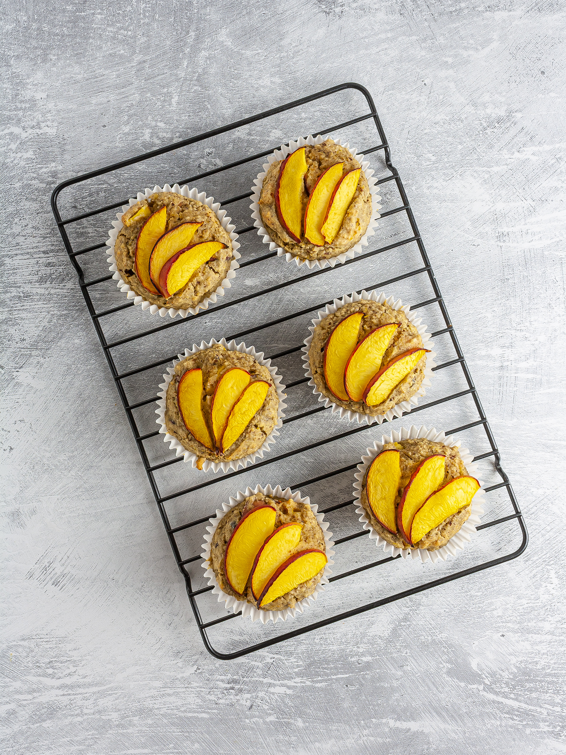 Baked peach muffins on a cooling rack