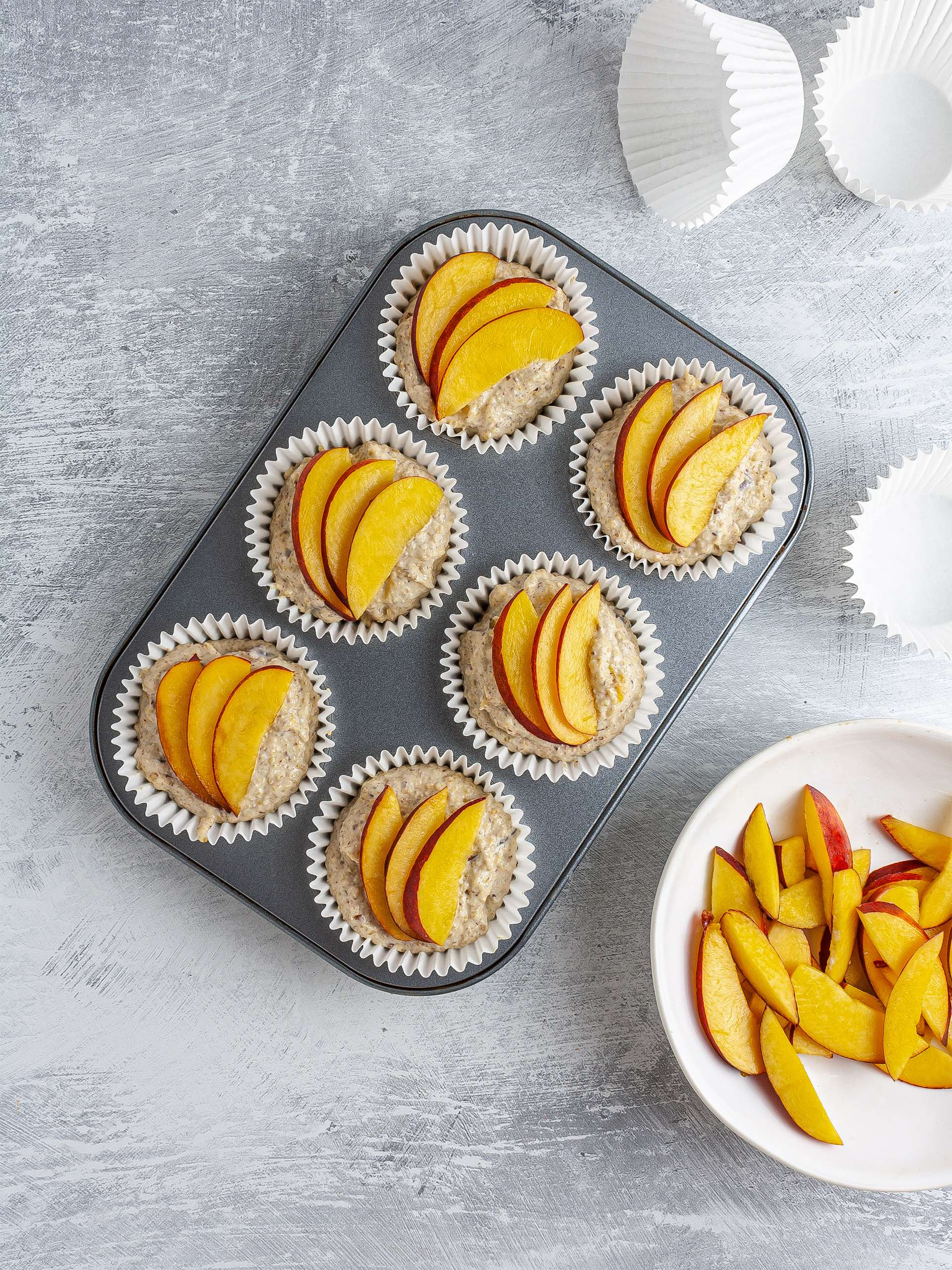 Muffin batter in cases topped with peach slices