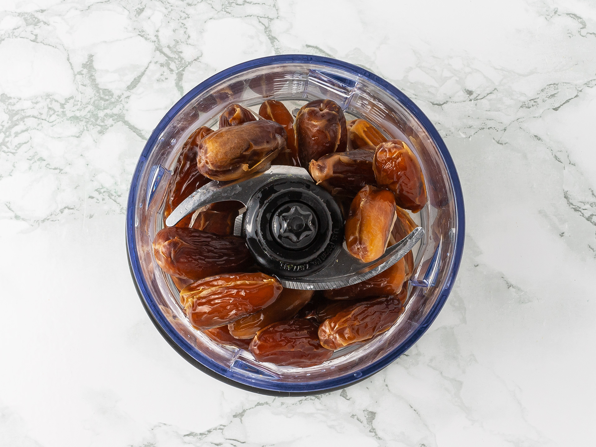 Pitted dates and water in a blender ready to be turned into a smooth paste