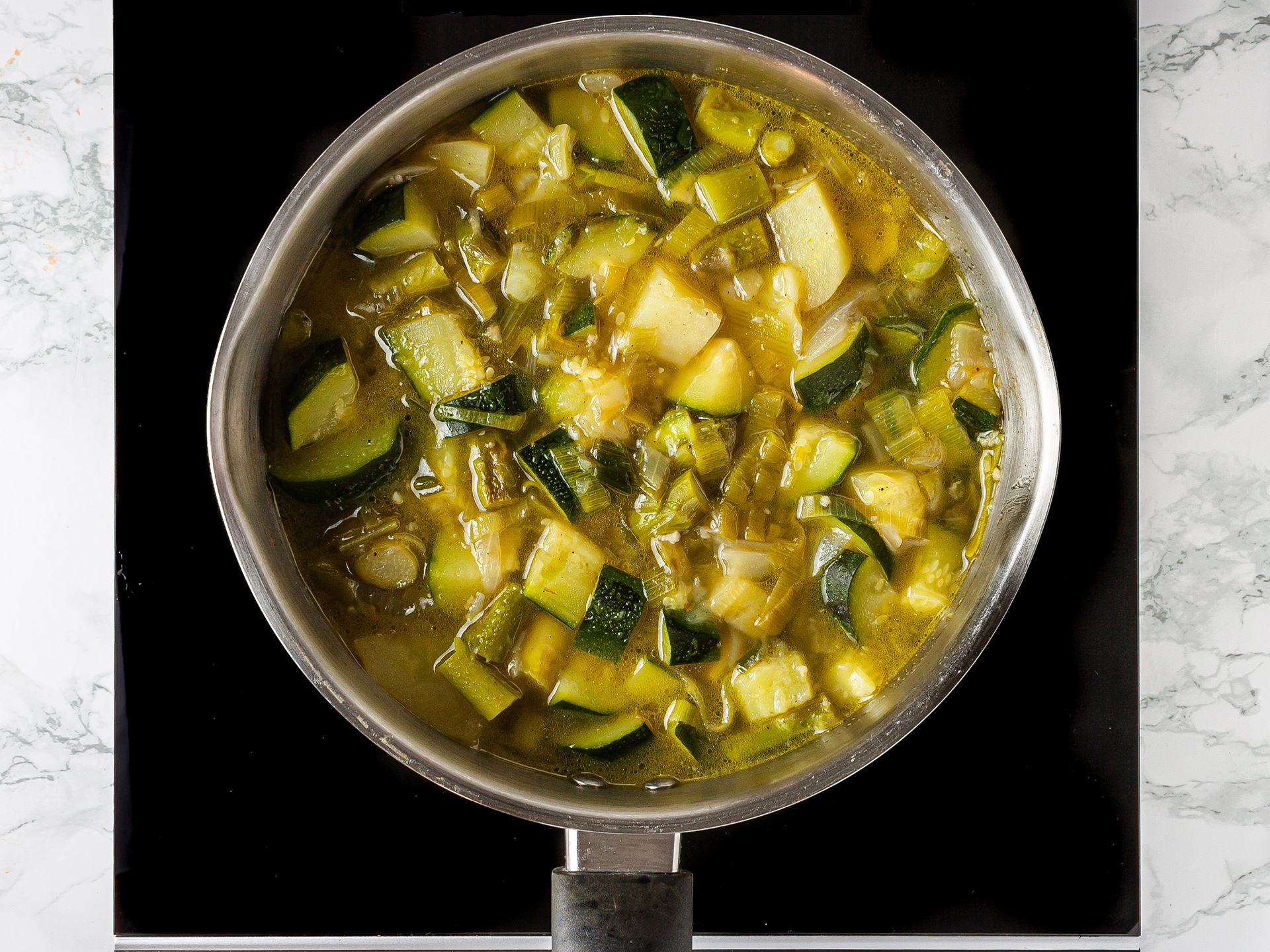 zucchini, asparagus, leek, and potato soup simmering in a pan
