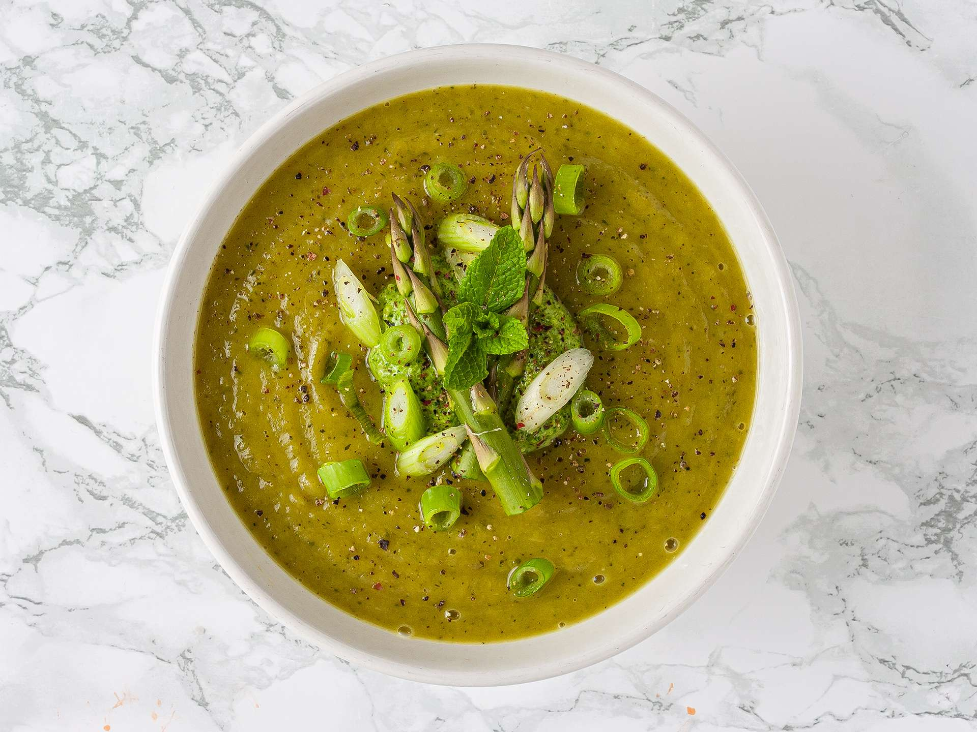 creamy asparagus and zucchini soup topped with watercress pesto, mint, and spring onions
