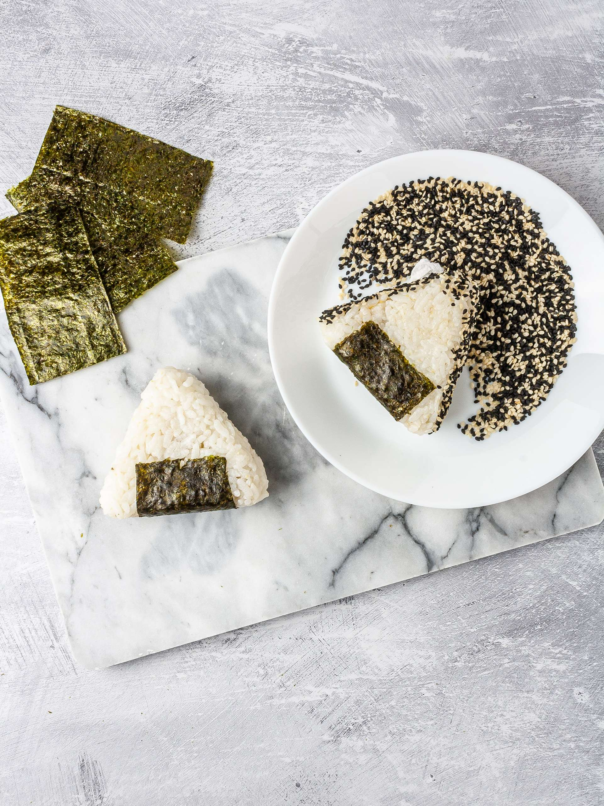 Vegan onigiri wrapped in nori sheet and coated in sesame seeds.