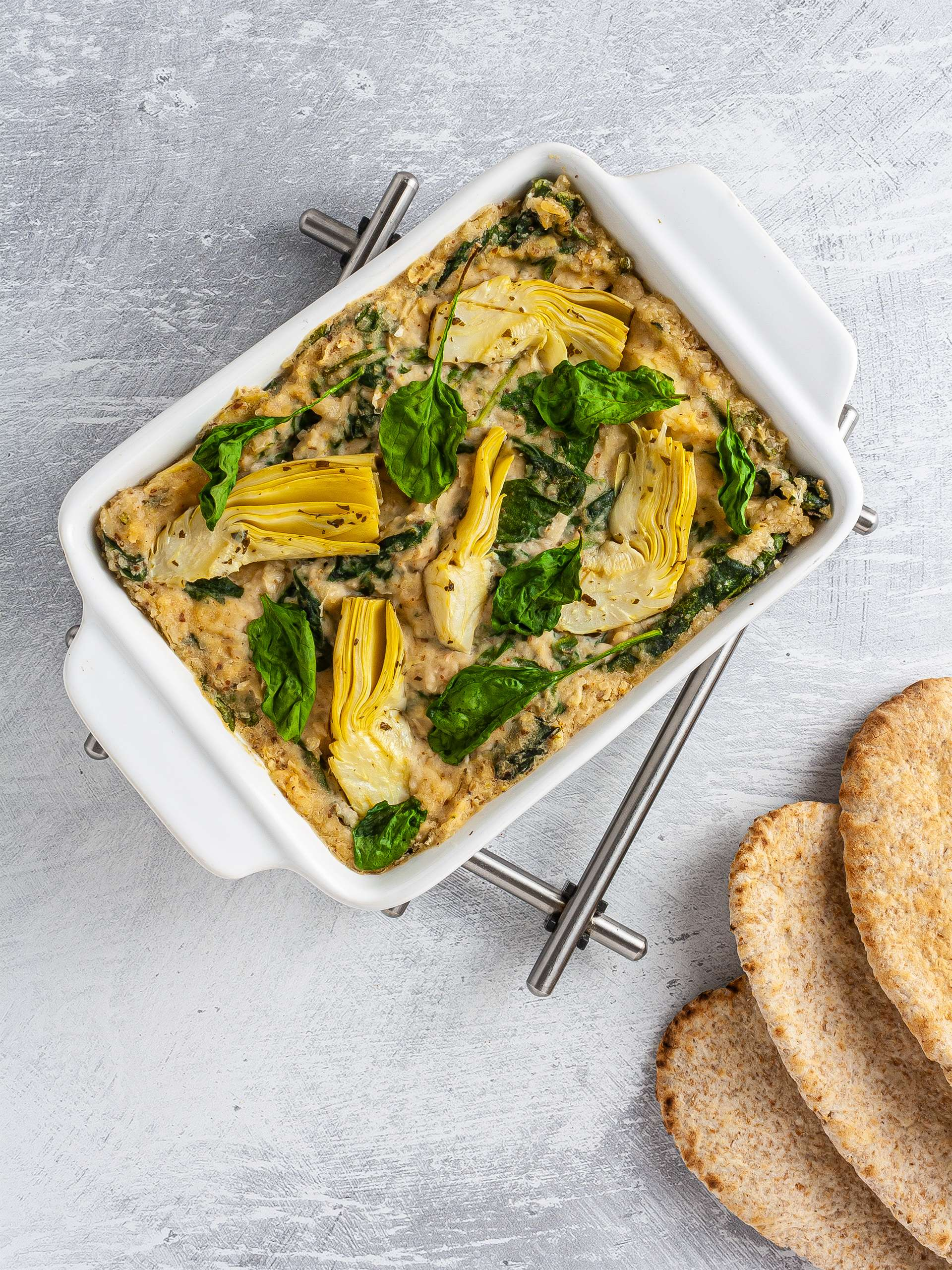 Baked spinach artichoke dip served with pitta bread.