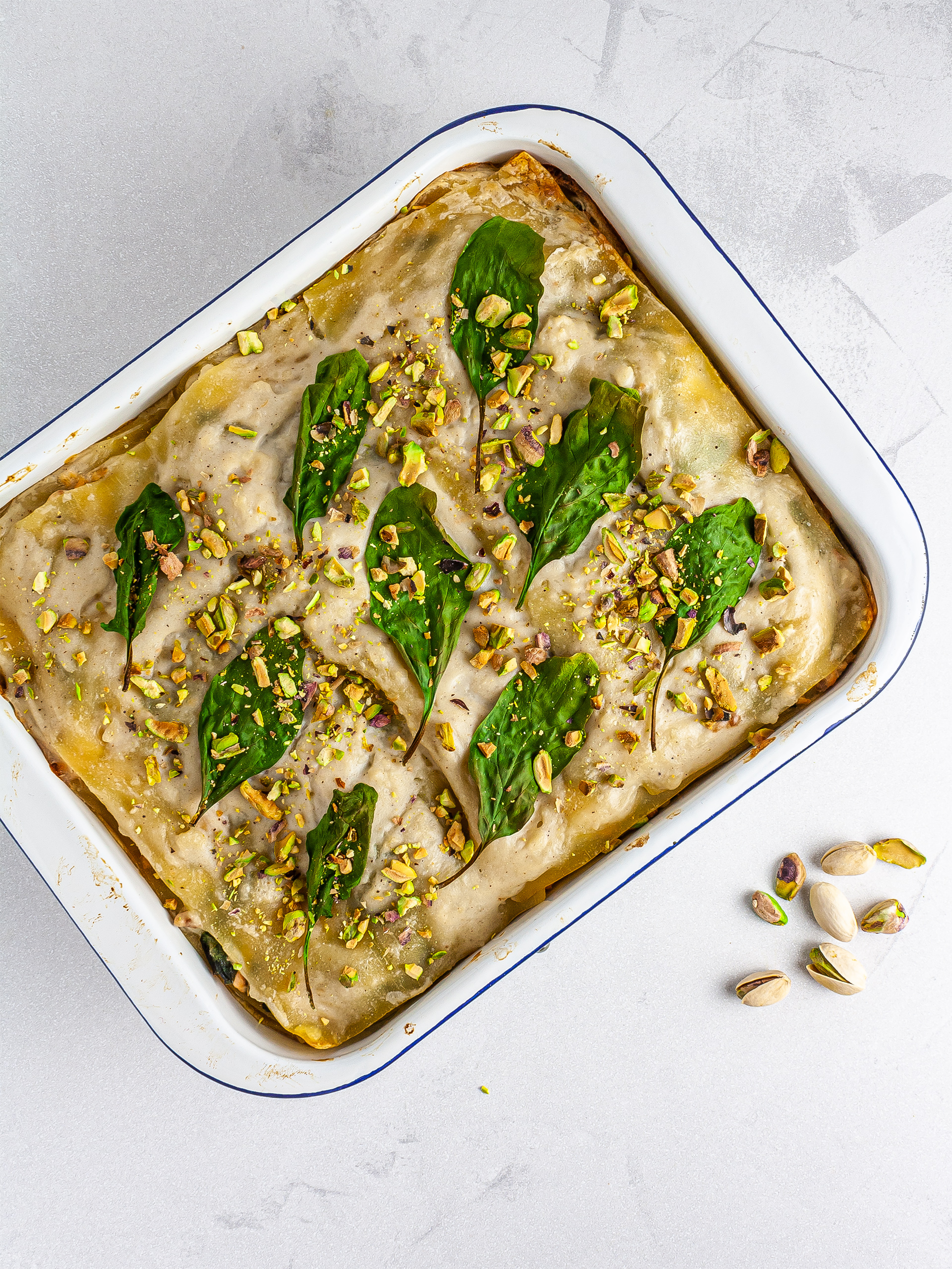 Baked spinach salmon lasagna topped with pistachio nuts