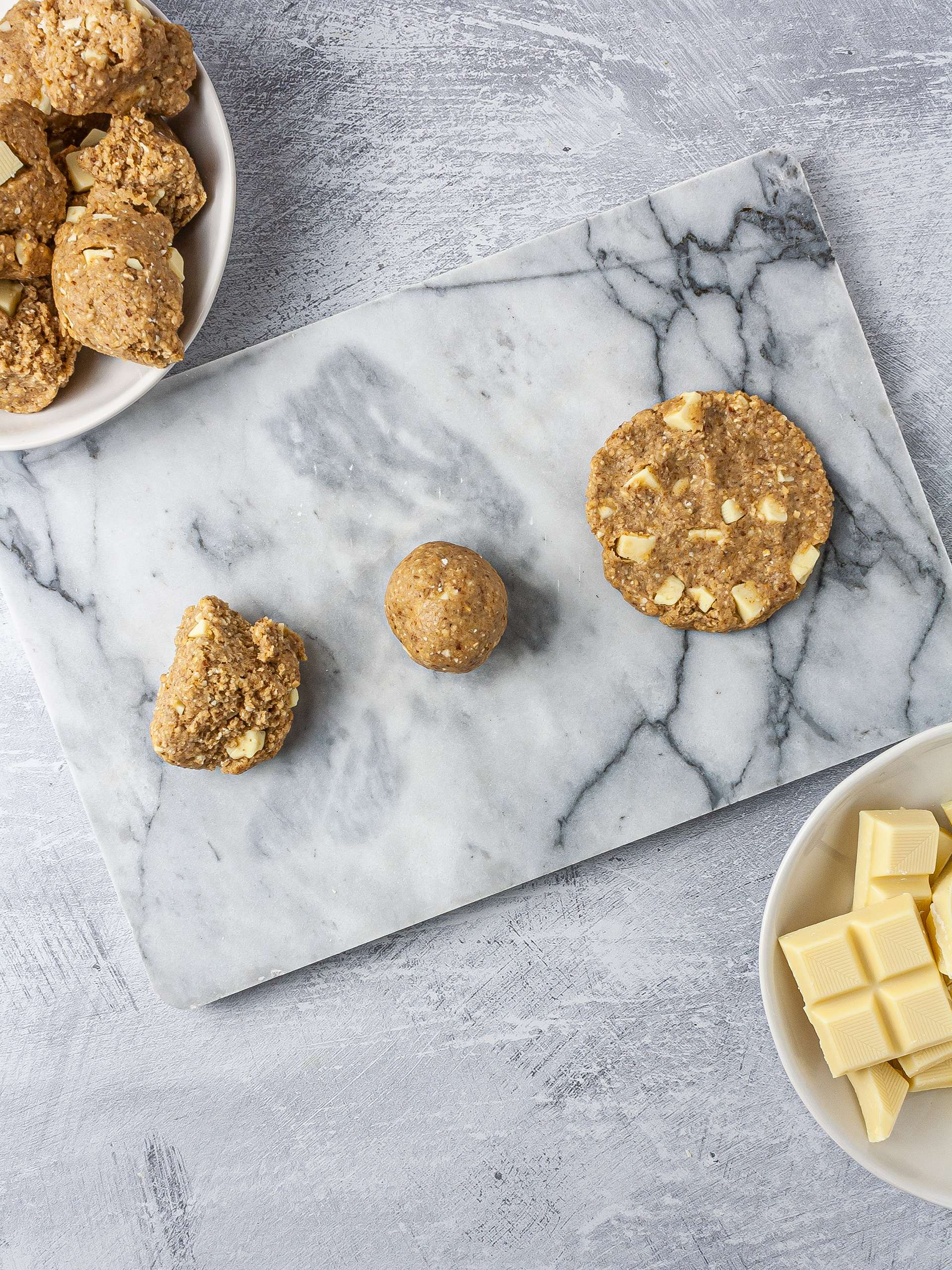 Vegan white chocolate cookie dough shaped as ball and then flattened as a cookie.