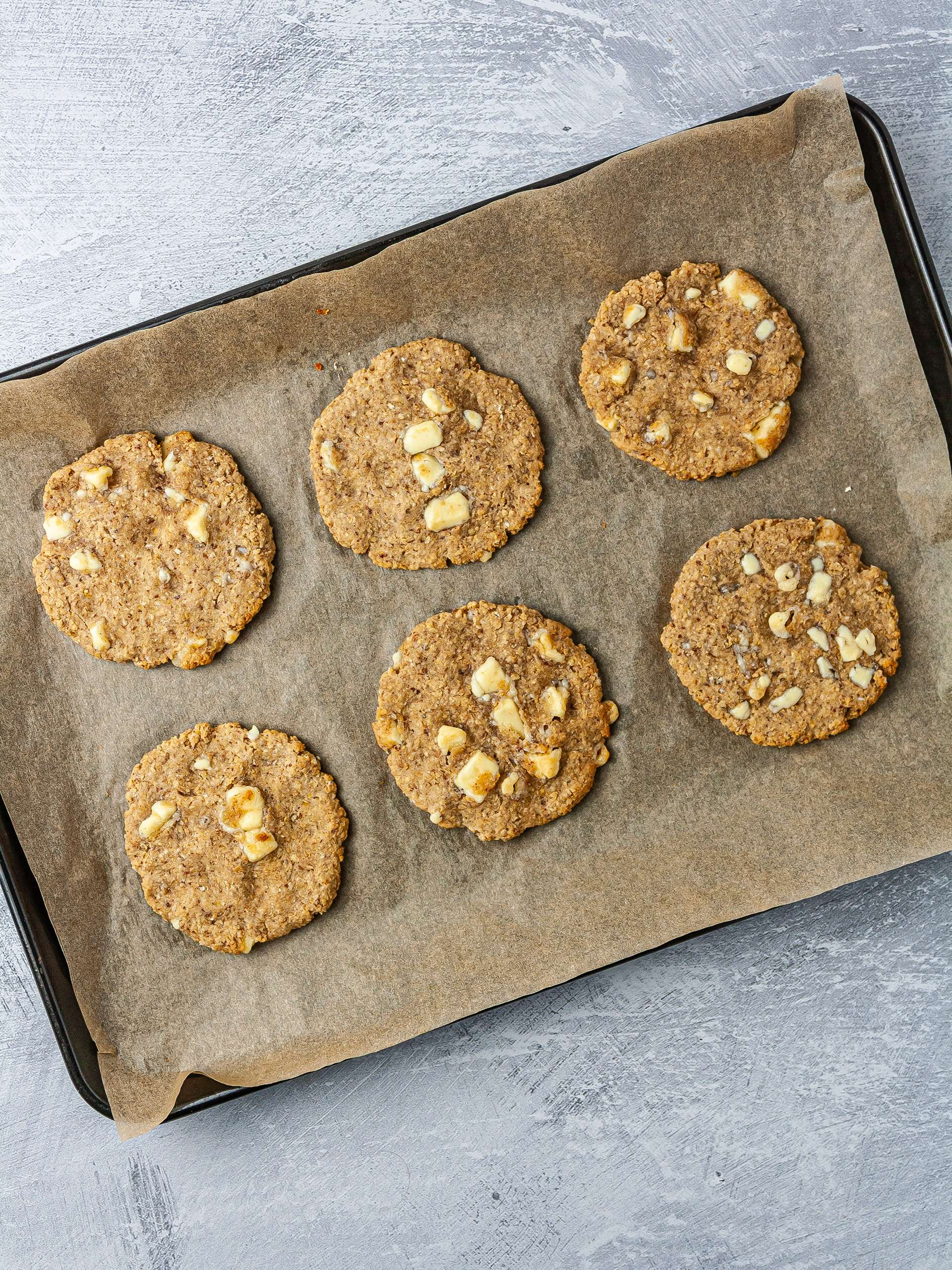 Vegan white chocolate chip cookies baked on a baking tray.