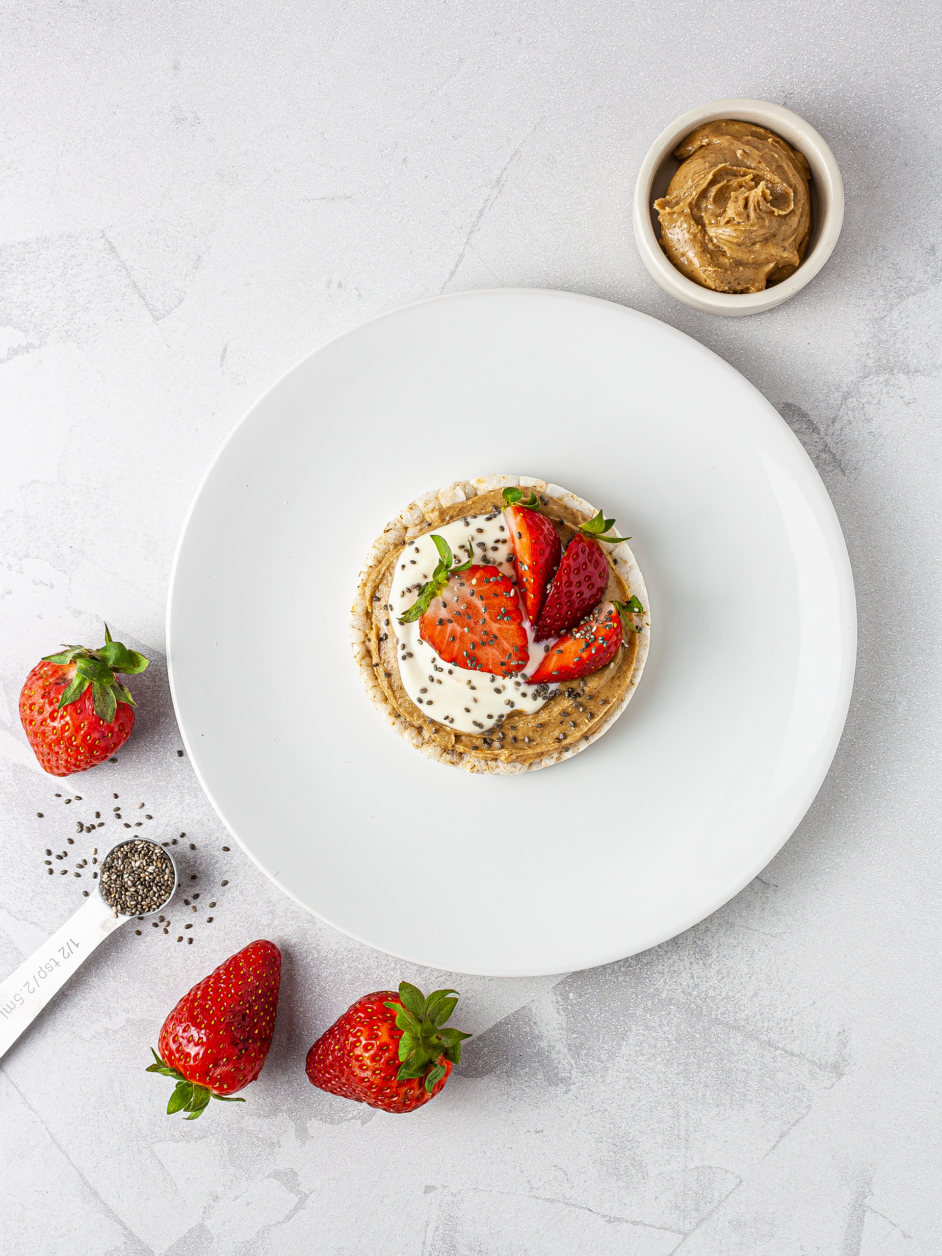 Rice cake with almond butter, yogurt, strawberries and chia seeds.