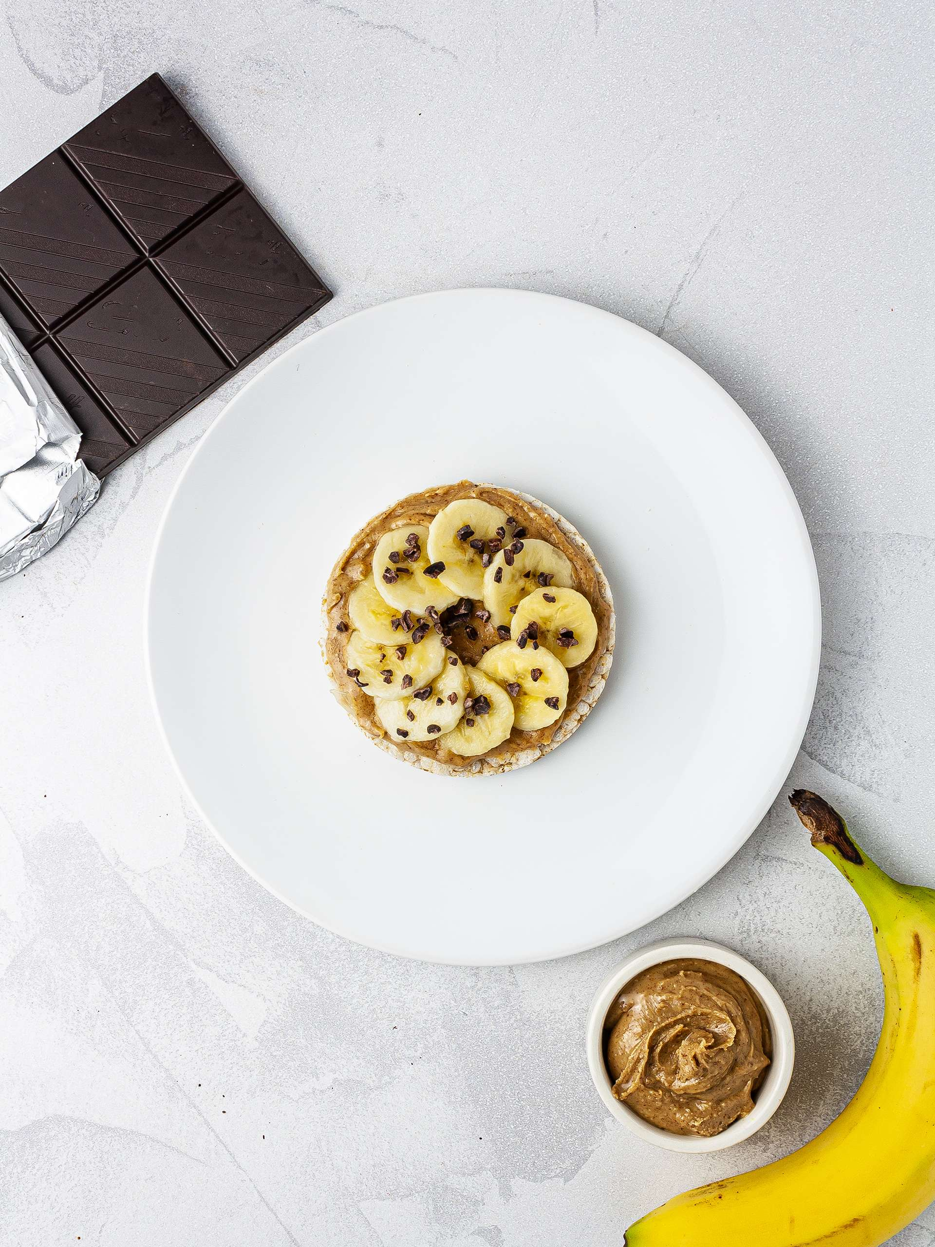 Rice cake with almond butter, sliced banana and chocolate chips.