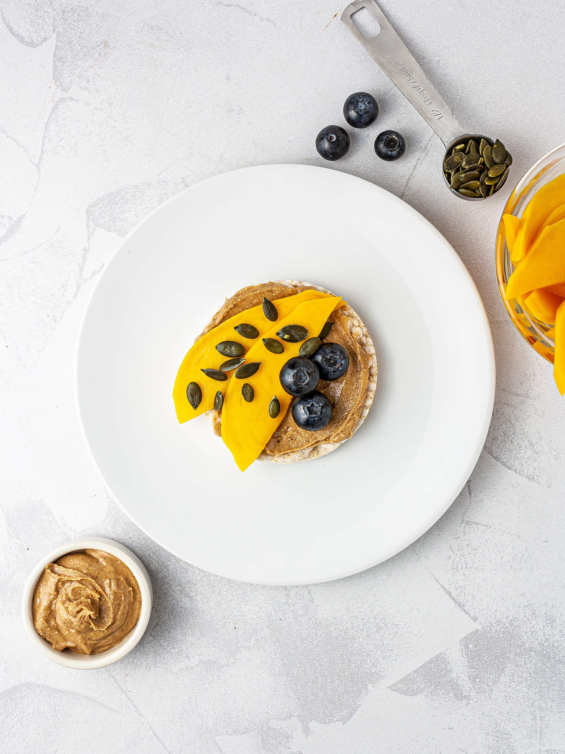 Rice cake with mango, blueberries and pumpkin seeds.