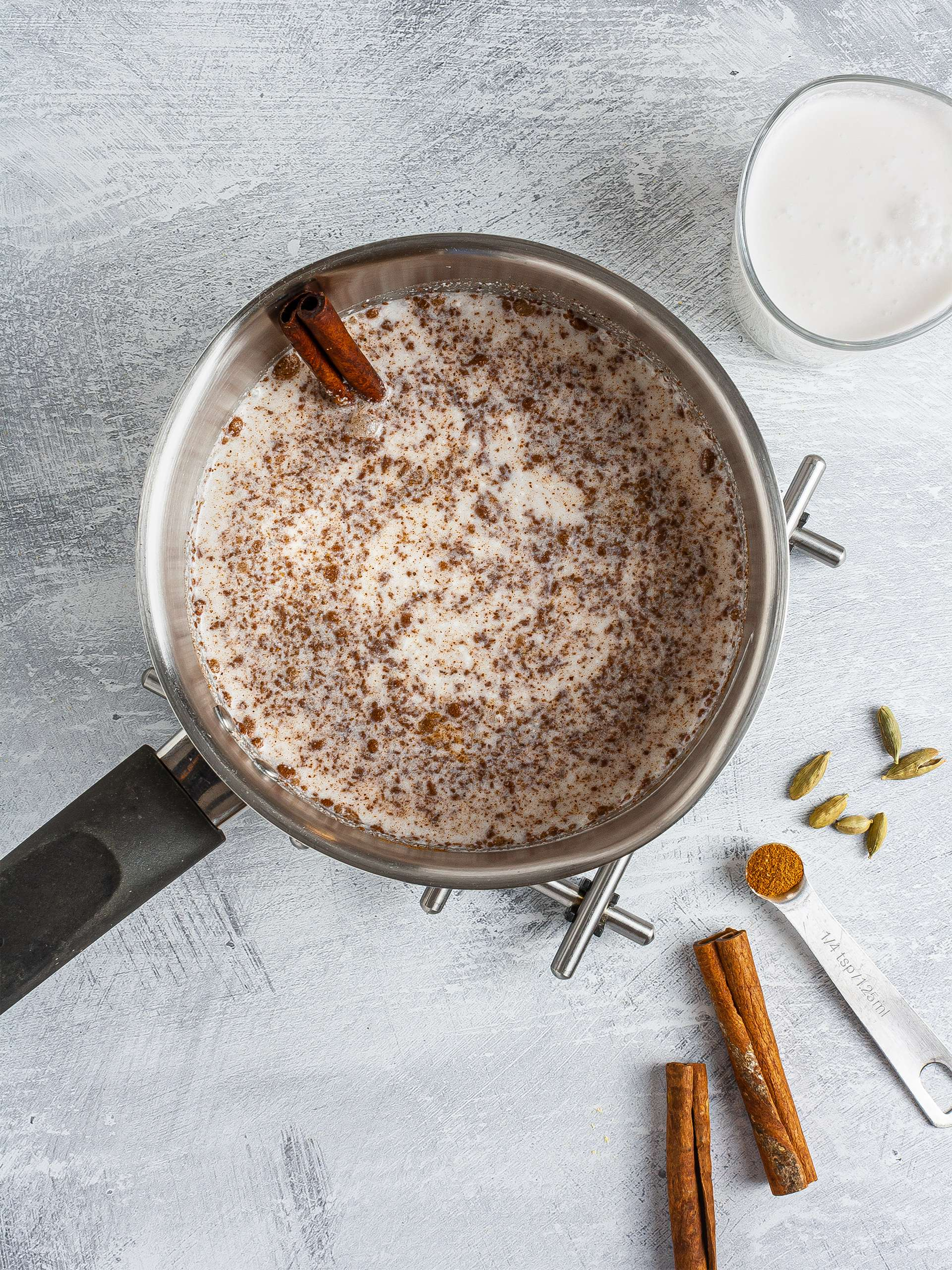 Coconut milk simmering with cinnamon and cardamom