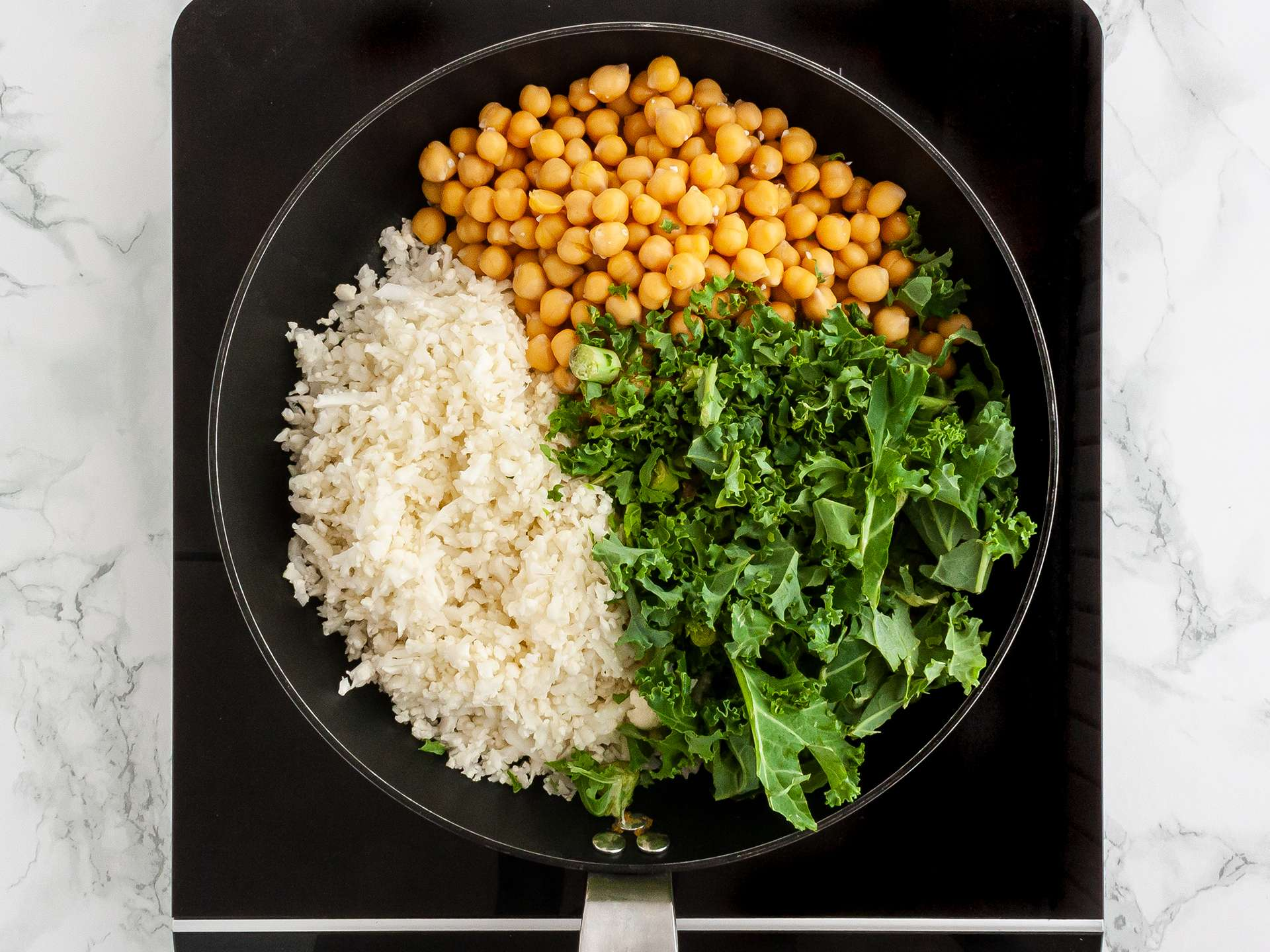 Cauliflower rice, kale, chickpeas cooking in a pan