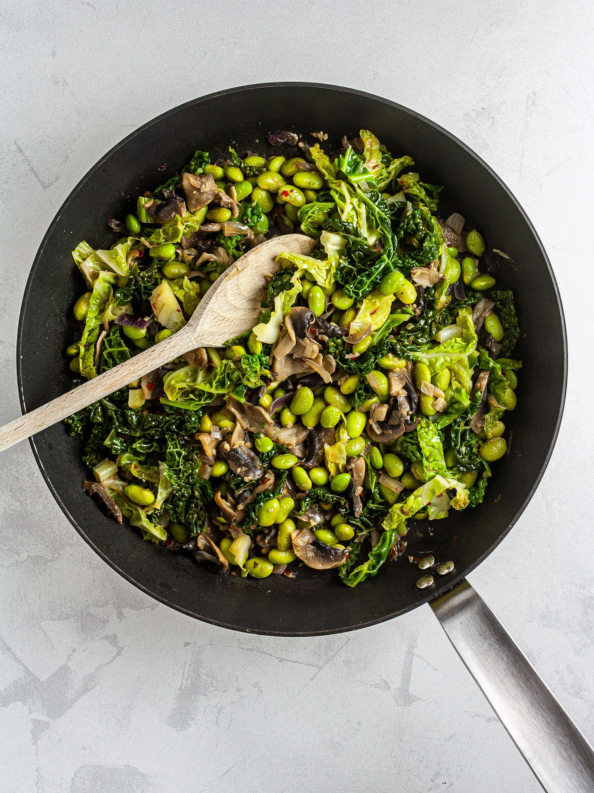 Cooked cabbage, mushroom, and edamame in a skillet