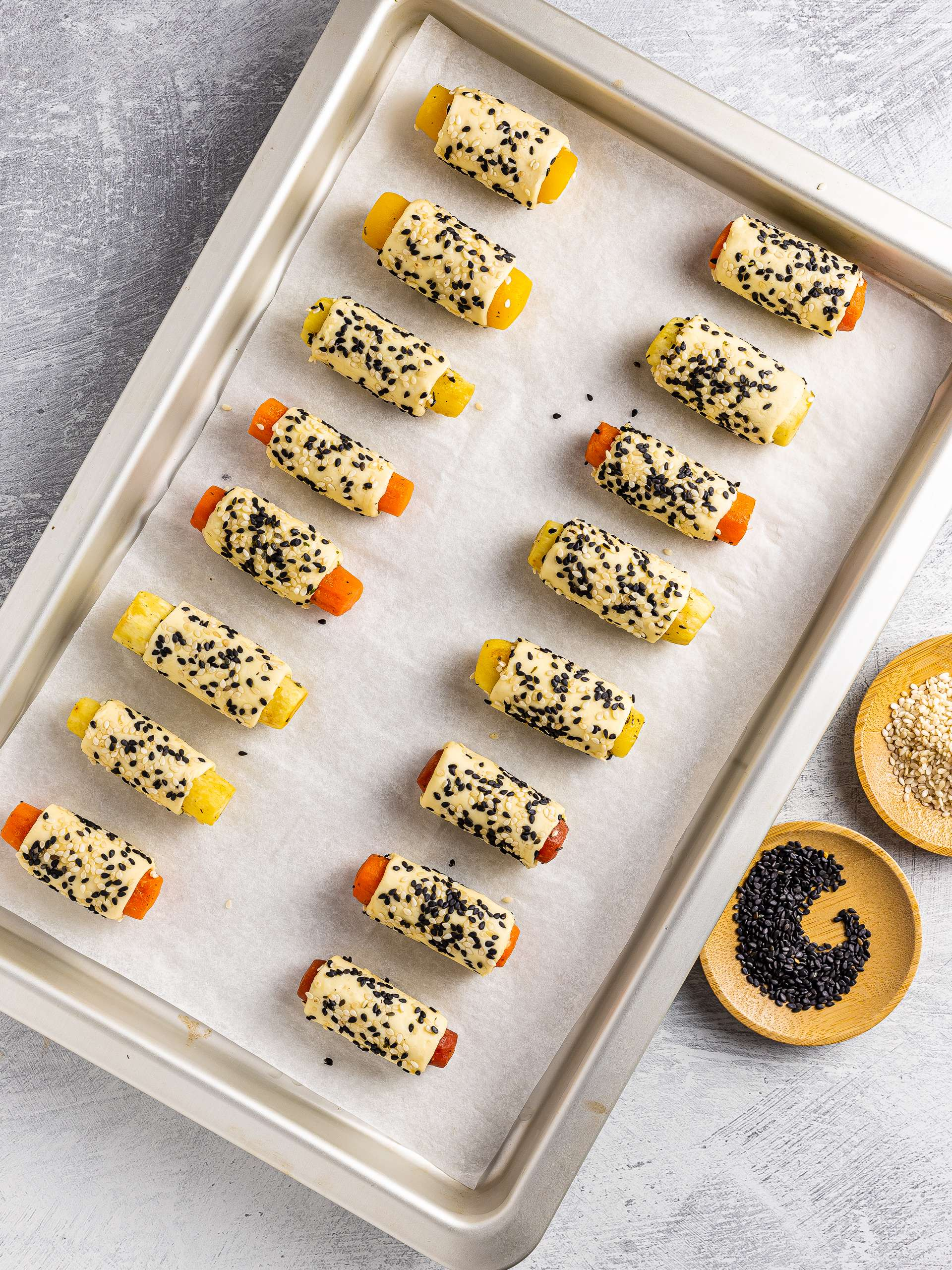 carrots pigs in a blanket pastries with sesame seeds