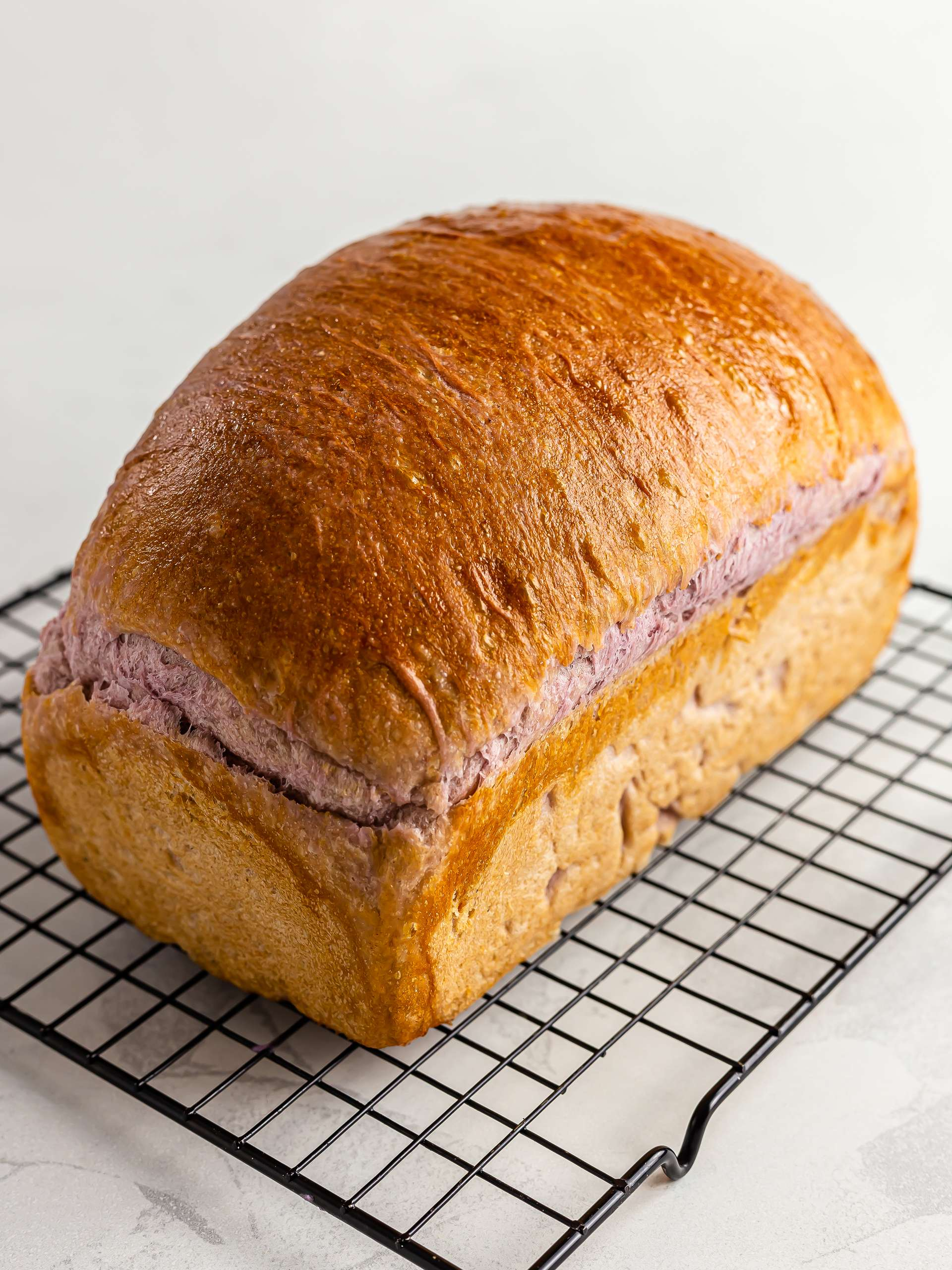 baked ube bread loaf cooling on a rack