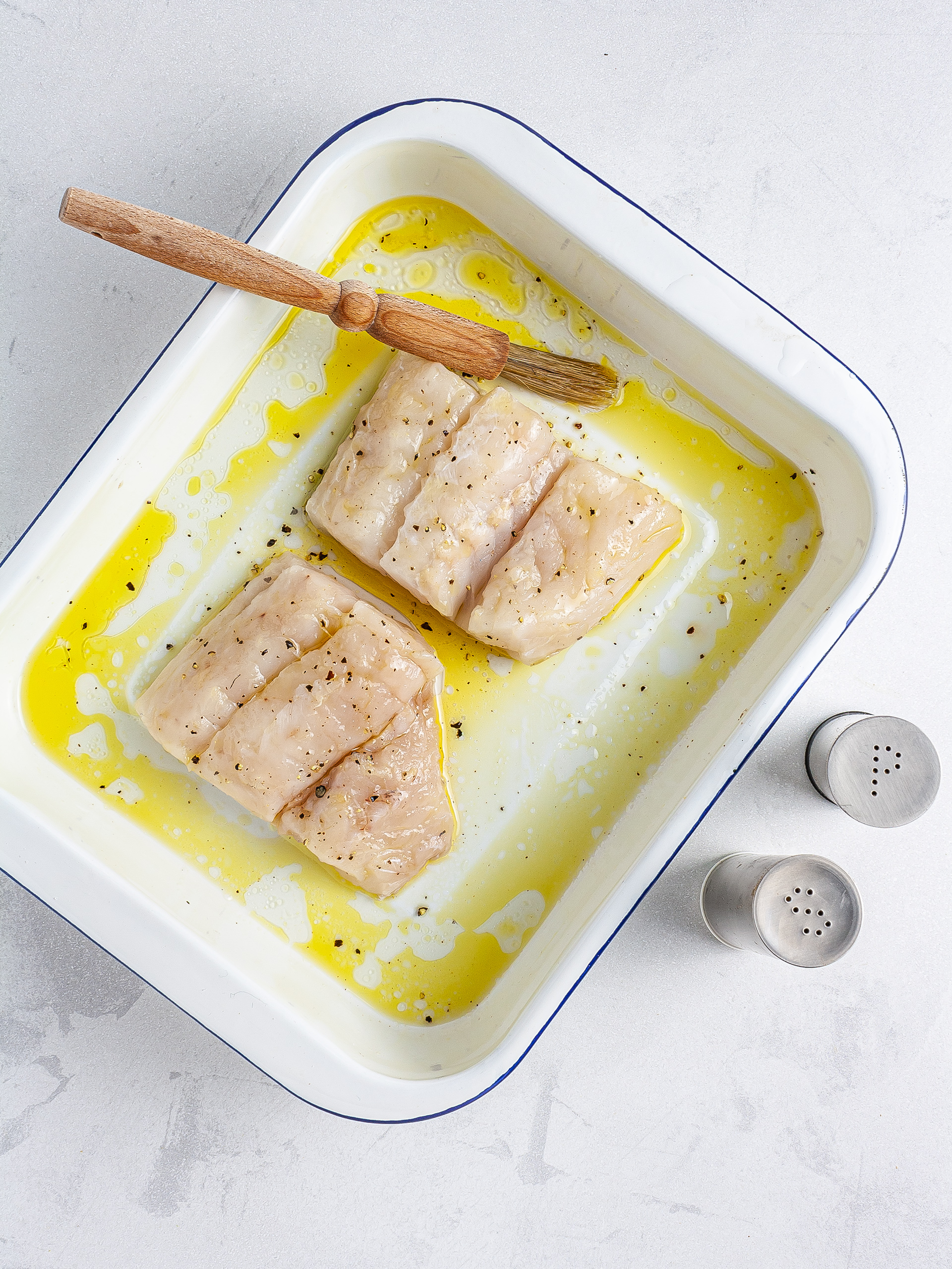 Hake fillet brushed with oil and seasoned with salt and pepper
