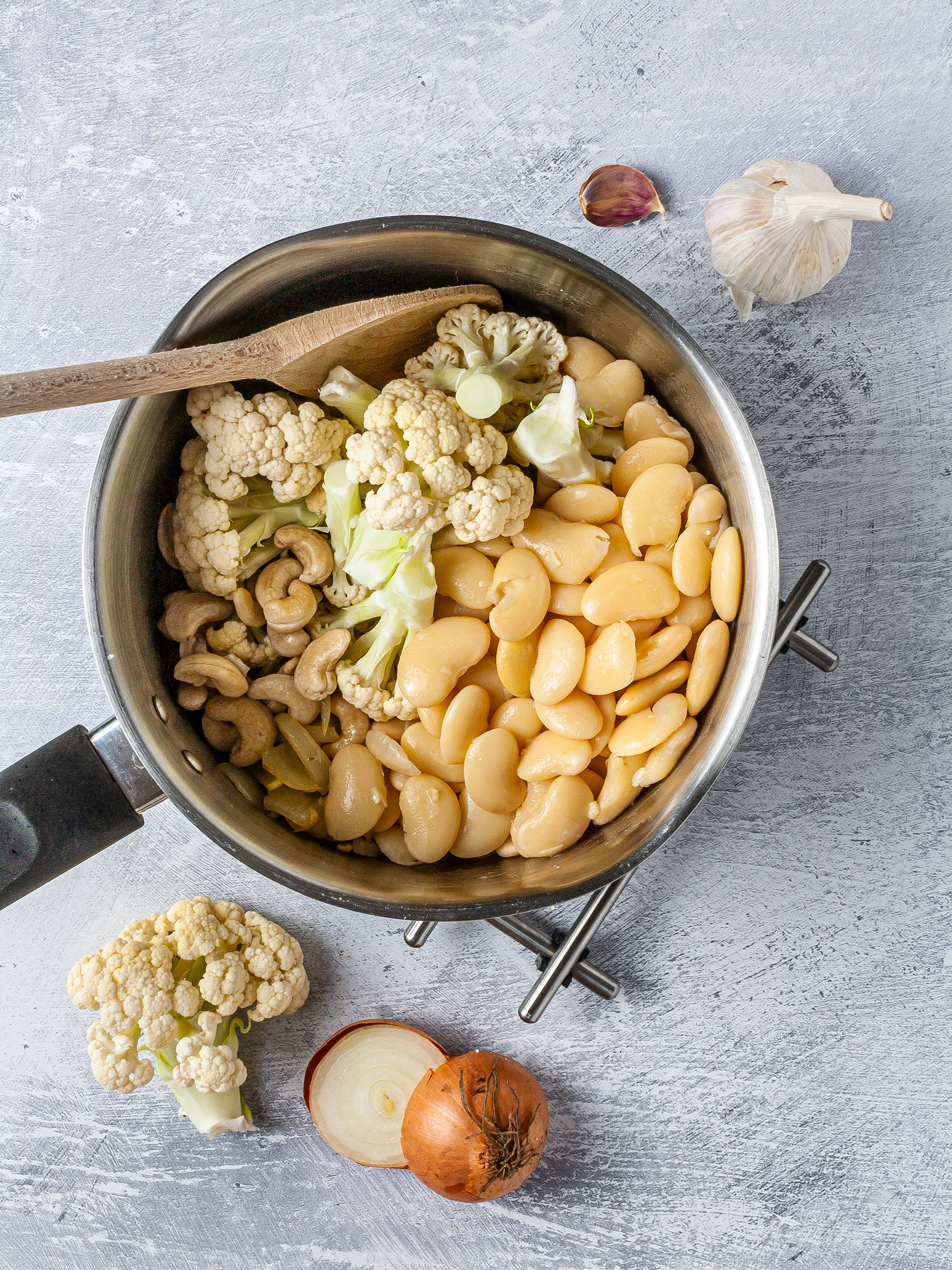 Onions, garlic, cauliflower, white beans in a pot