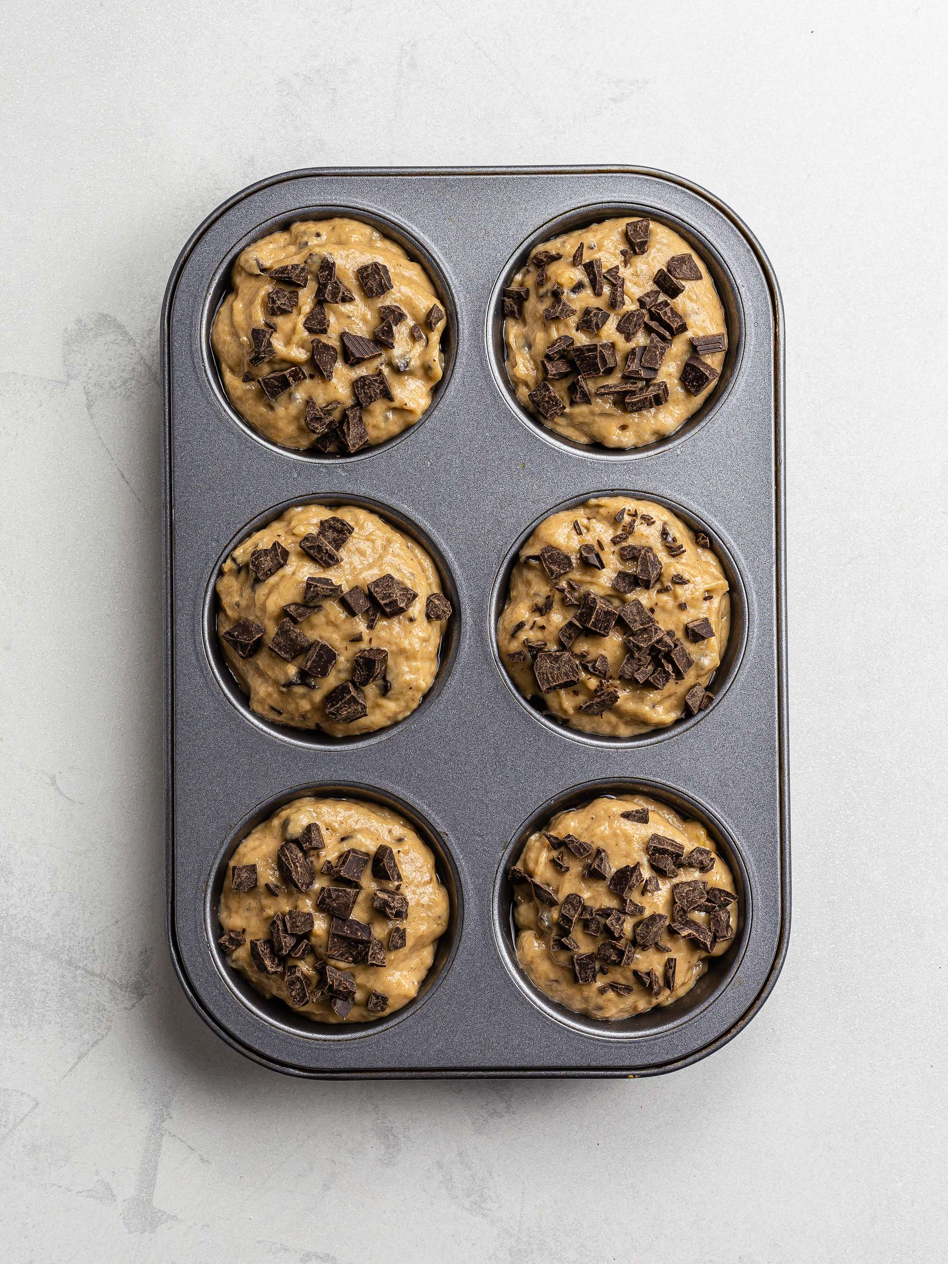 plantain muffins in a tin with chocolate chips