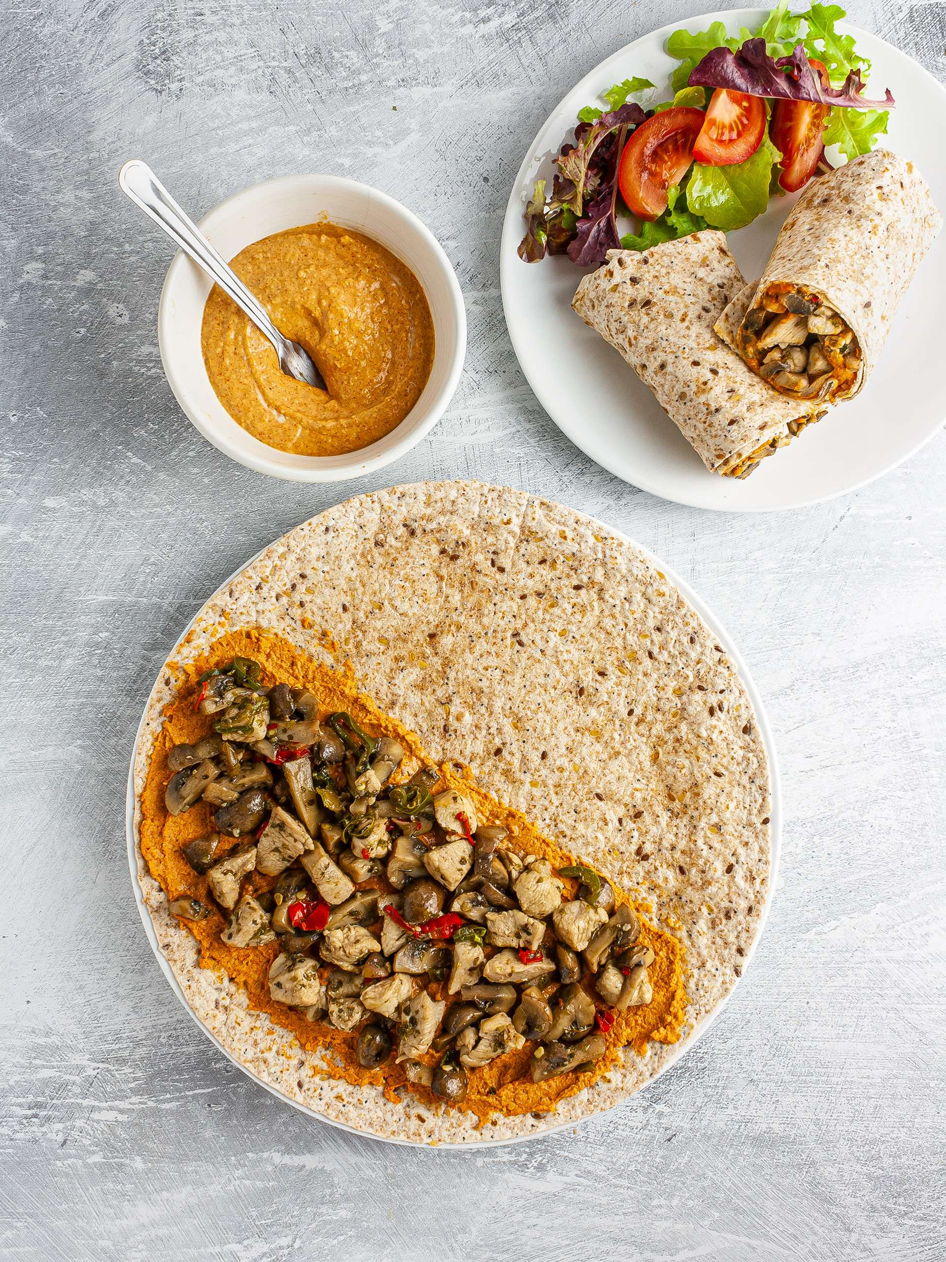 Wrap with paprika hummus, mushroom, and chicken served with a side salad