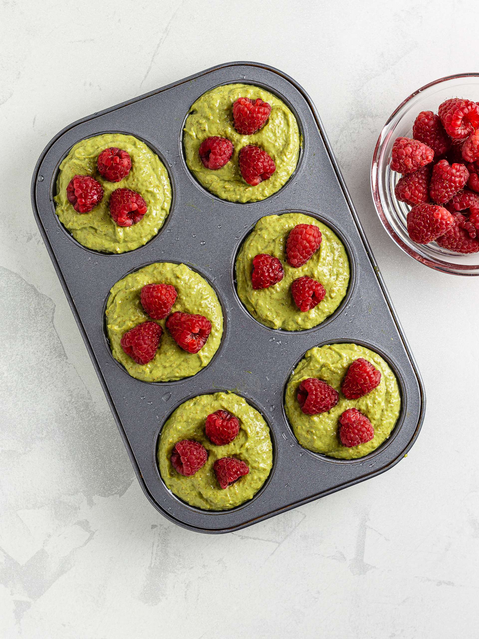 matcha muffins batter in a muffin tray with raspberries