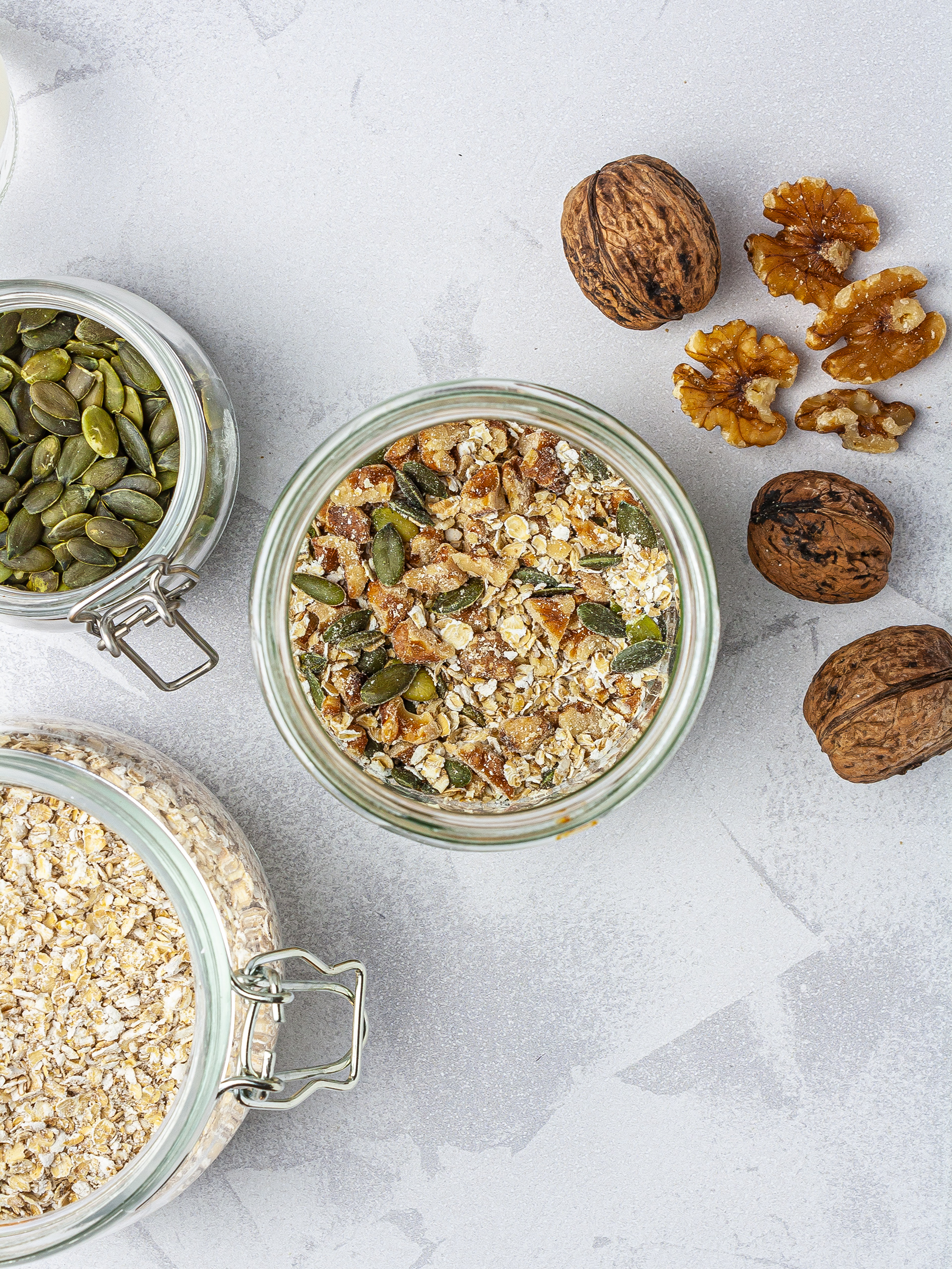 Granola layer in the smoothie jar with oats, walnut pieces, and pumpkin seeds.