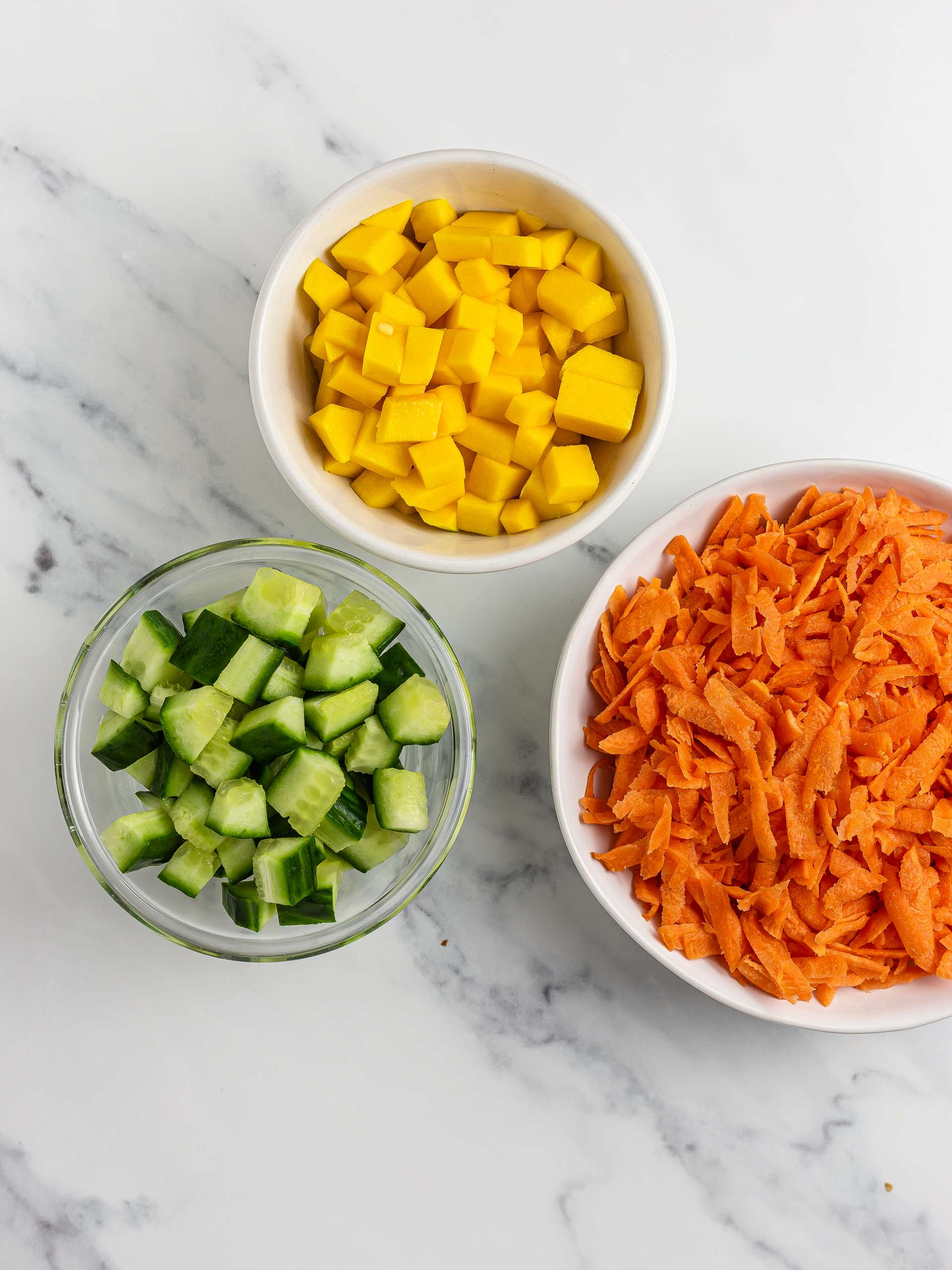 grated carrots and chopped cucumber and mango