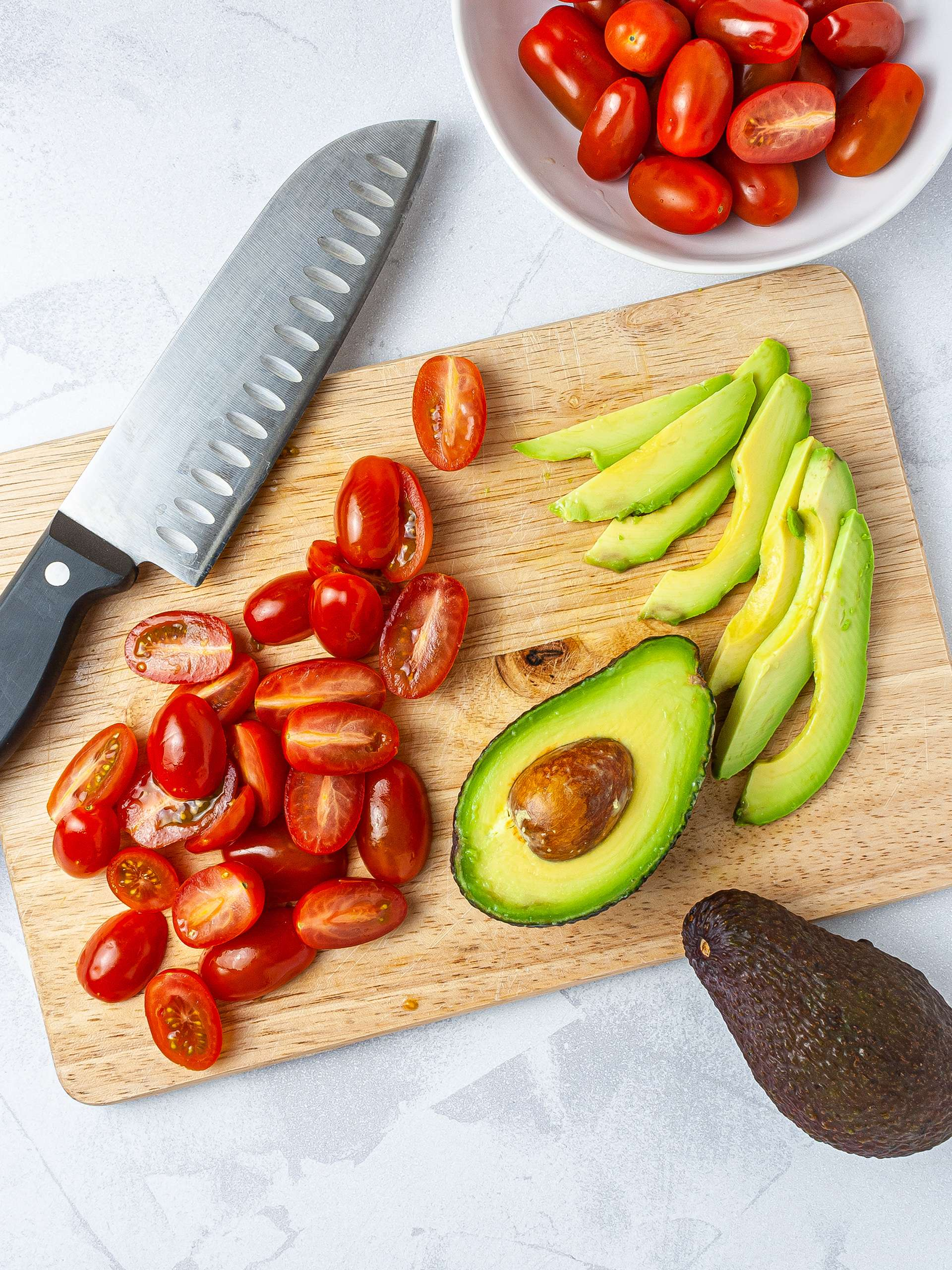 Halved tomatoes and sliced avocado on a chopping board.