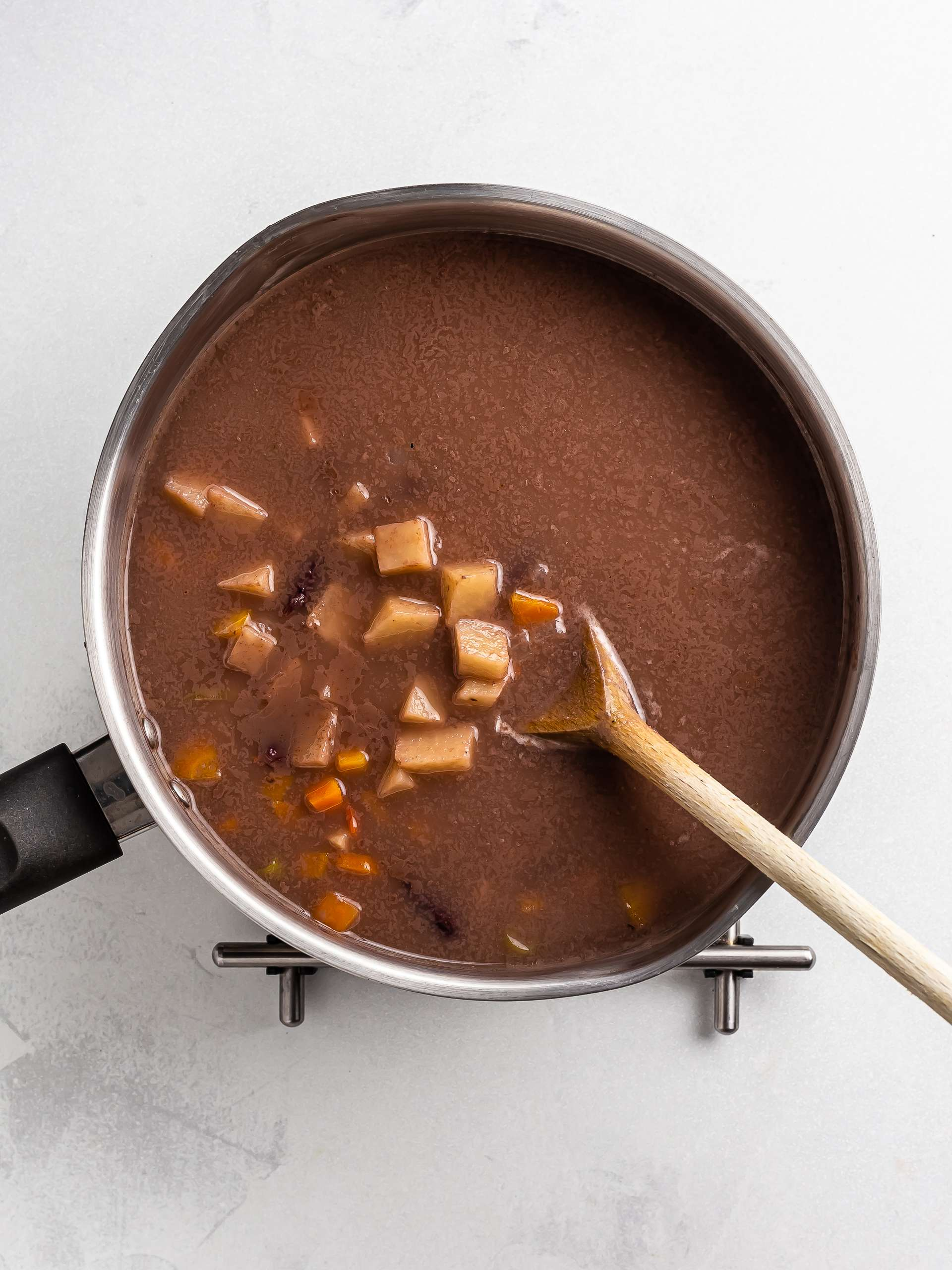 red pea soup cooking in a pot with yam and carrots