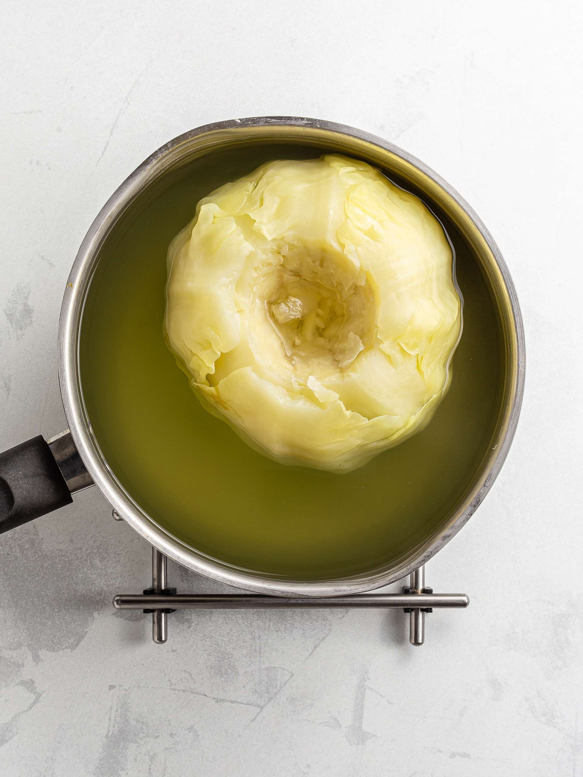 head of cabbage cooking in a pot