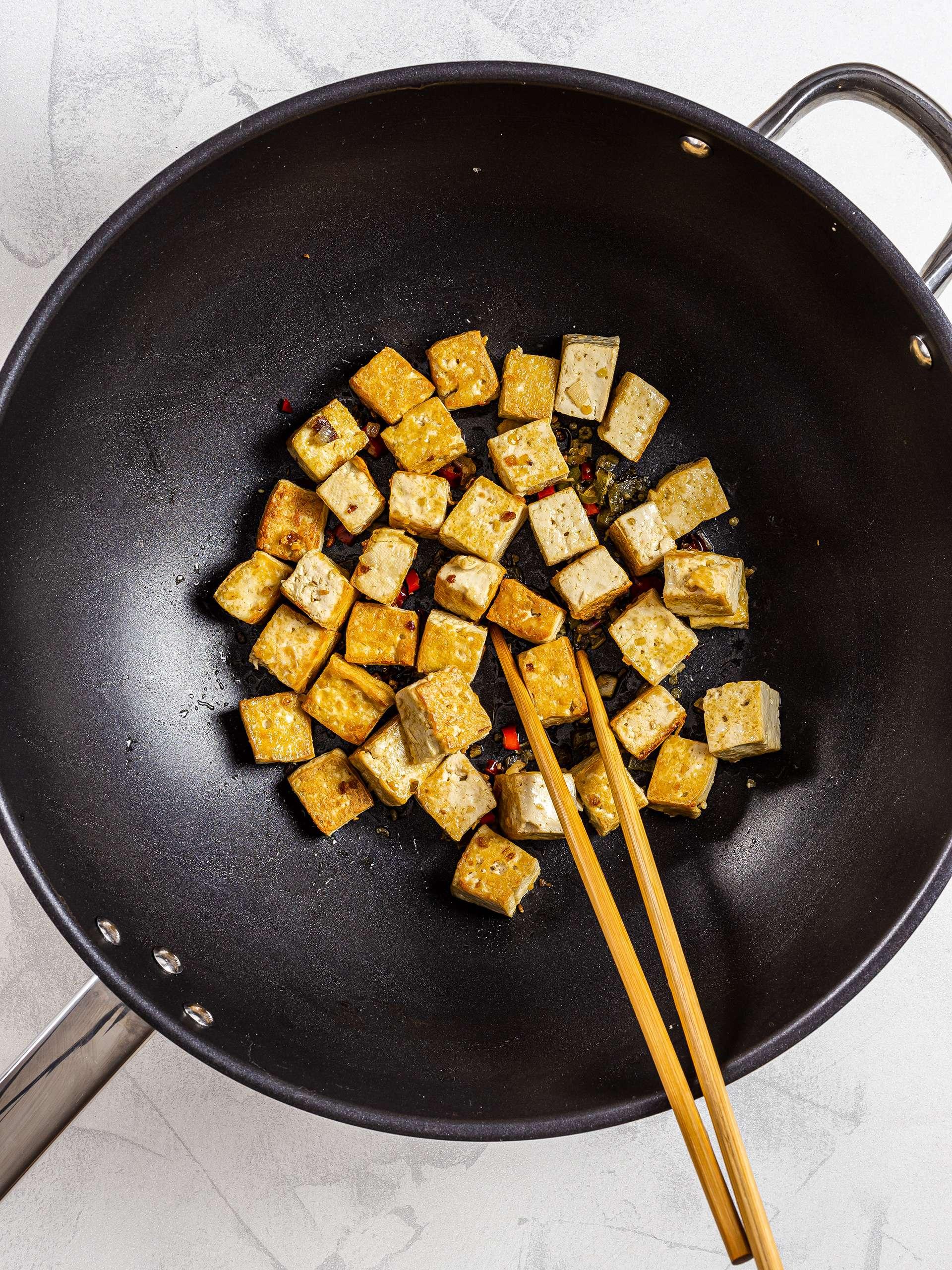 Seared tofu cubes in a wok