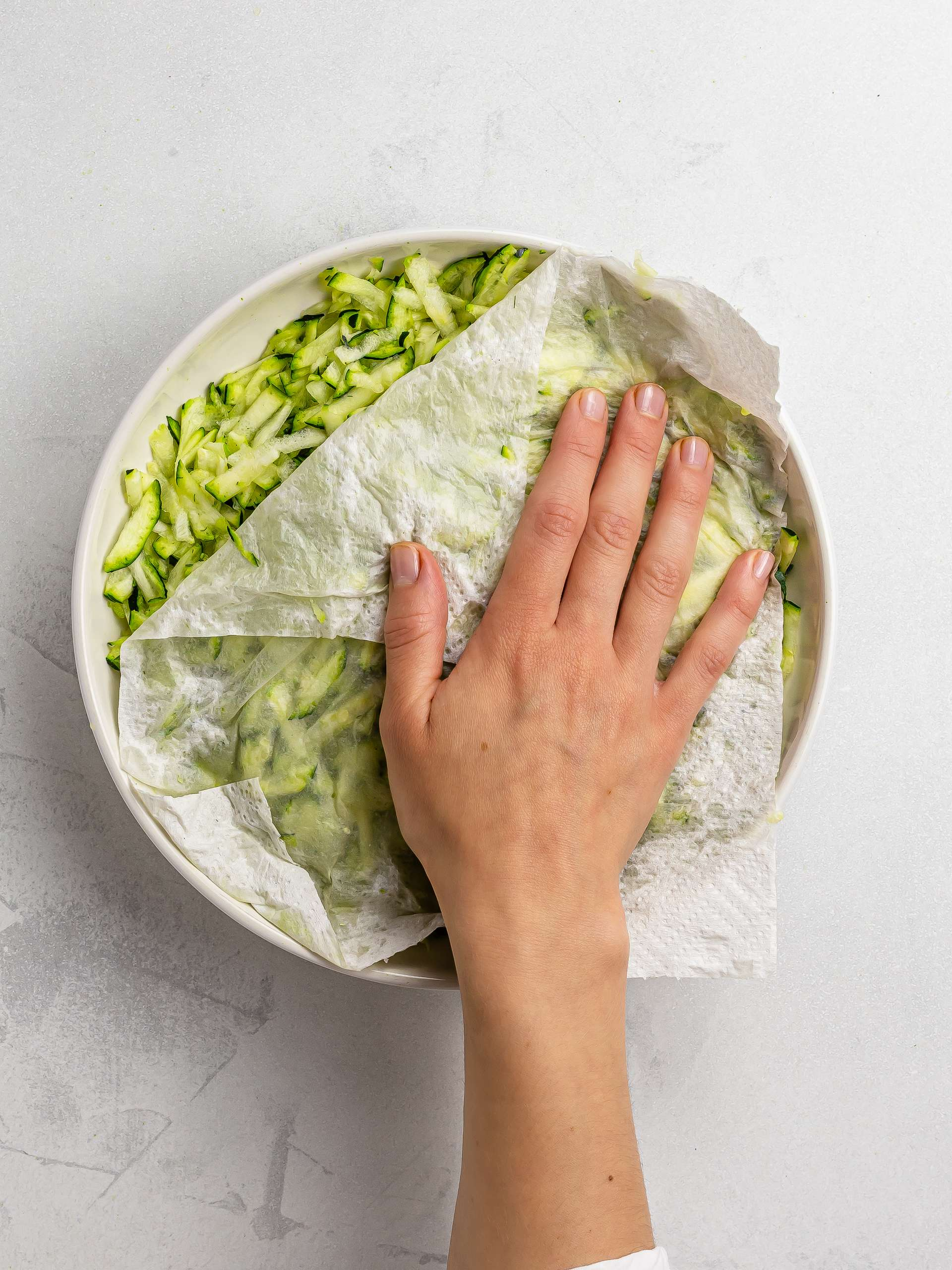 hand patting grated zucchini with kitchen paper