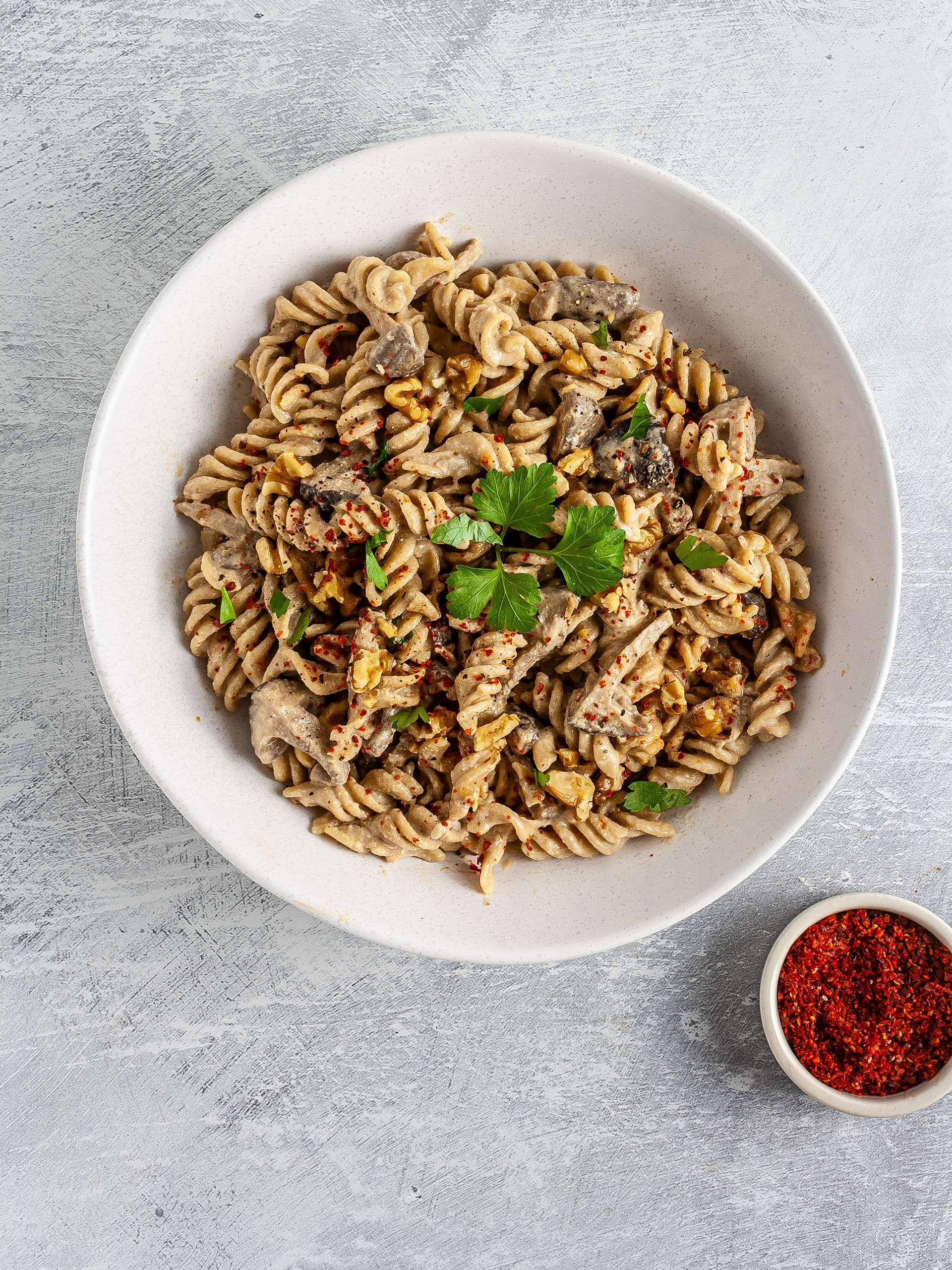 Mushroom tahini pasta with chillies, walnuts, and parsley